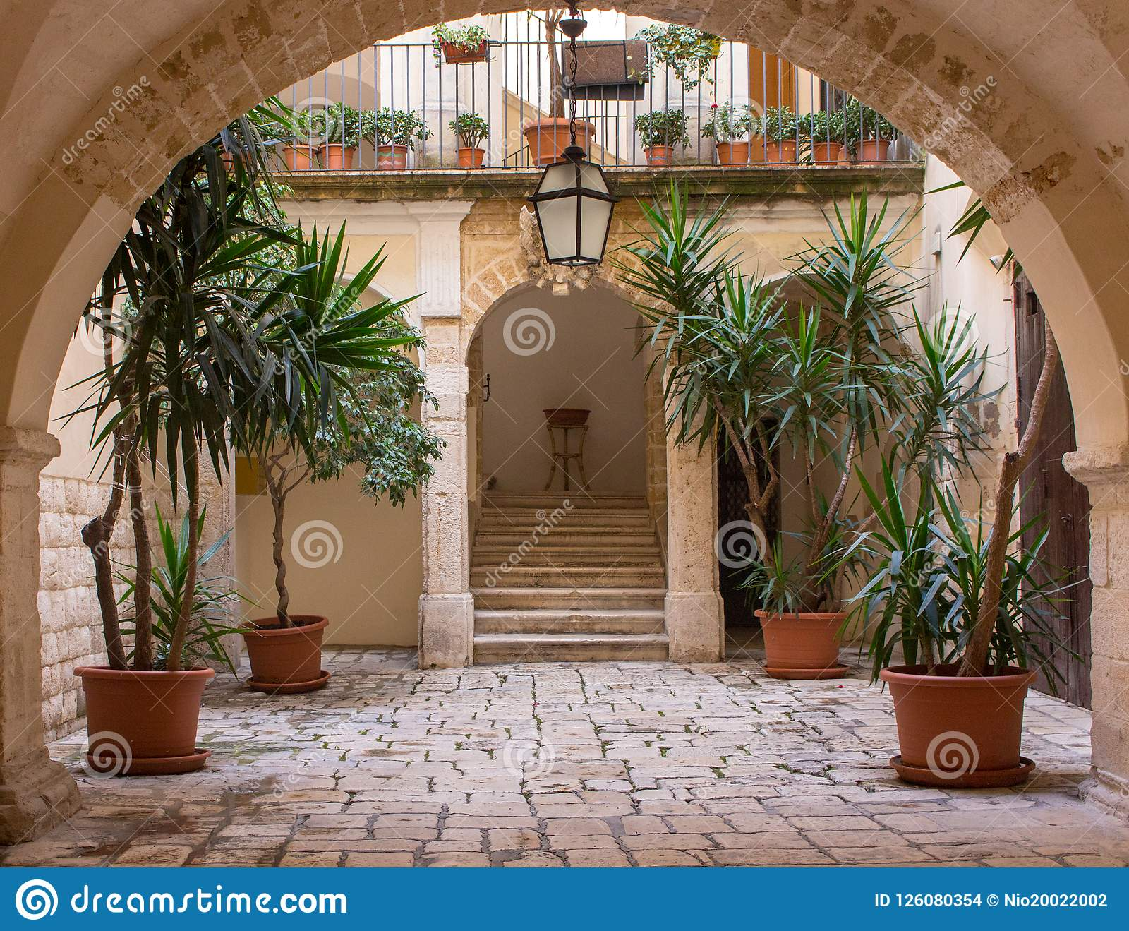 Backyard with arch plants in pots stairs and lantern. Patio decoration. Ancient courtyard background. Medieval architecture. & Backyard With Arch Plants In Pots Stairs And Lantern. Patio ...