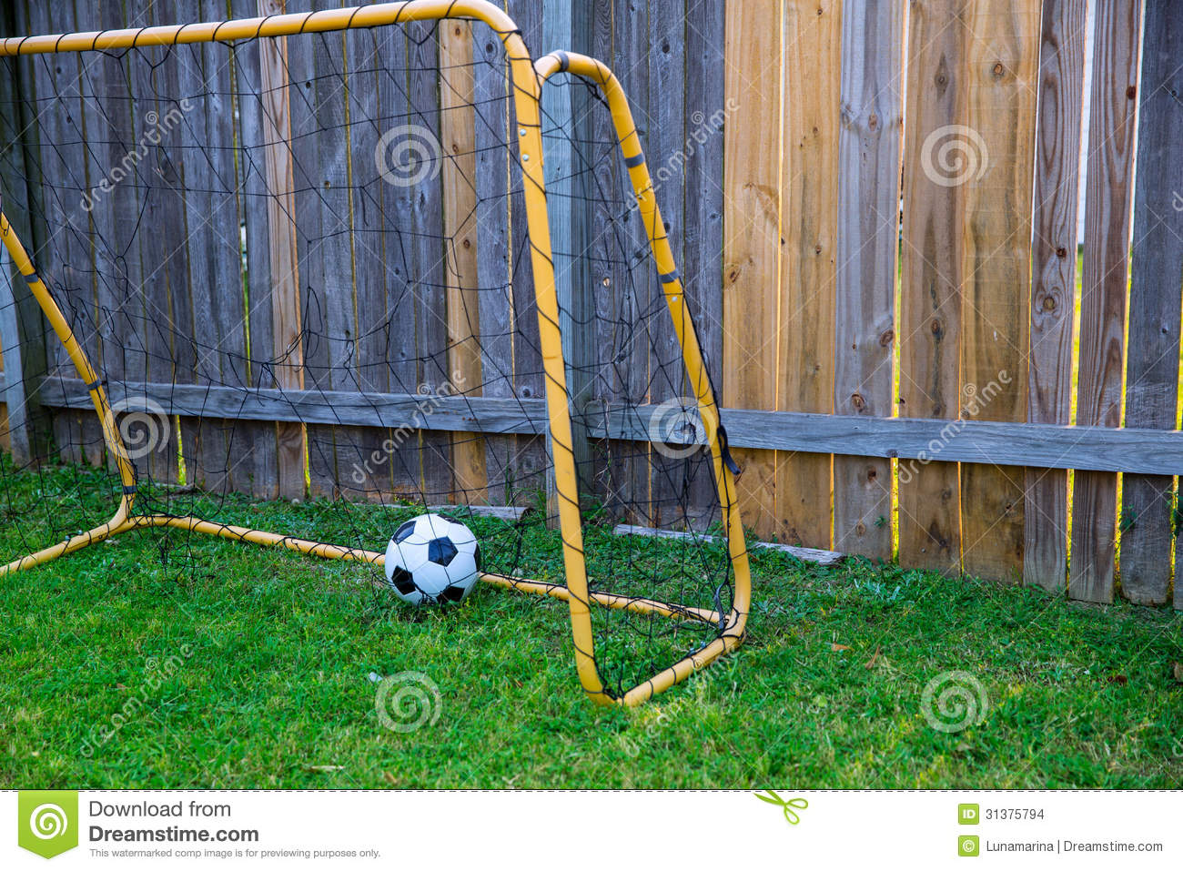backyard chldren soccer goal at the wood fence with leather ball on