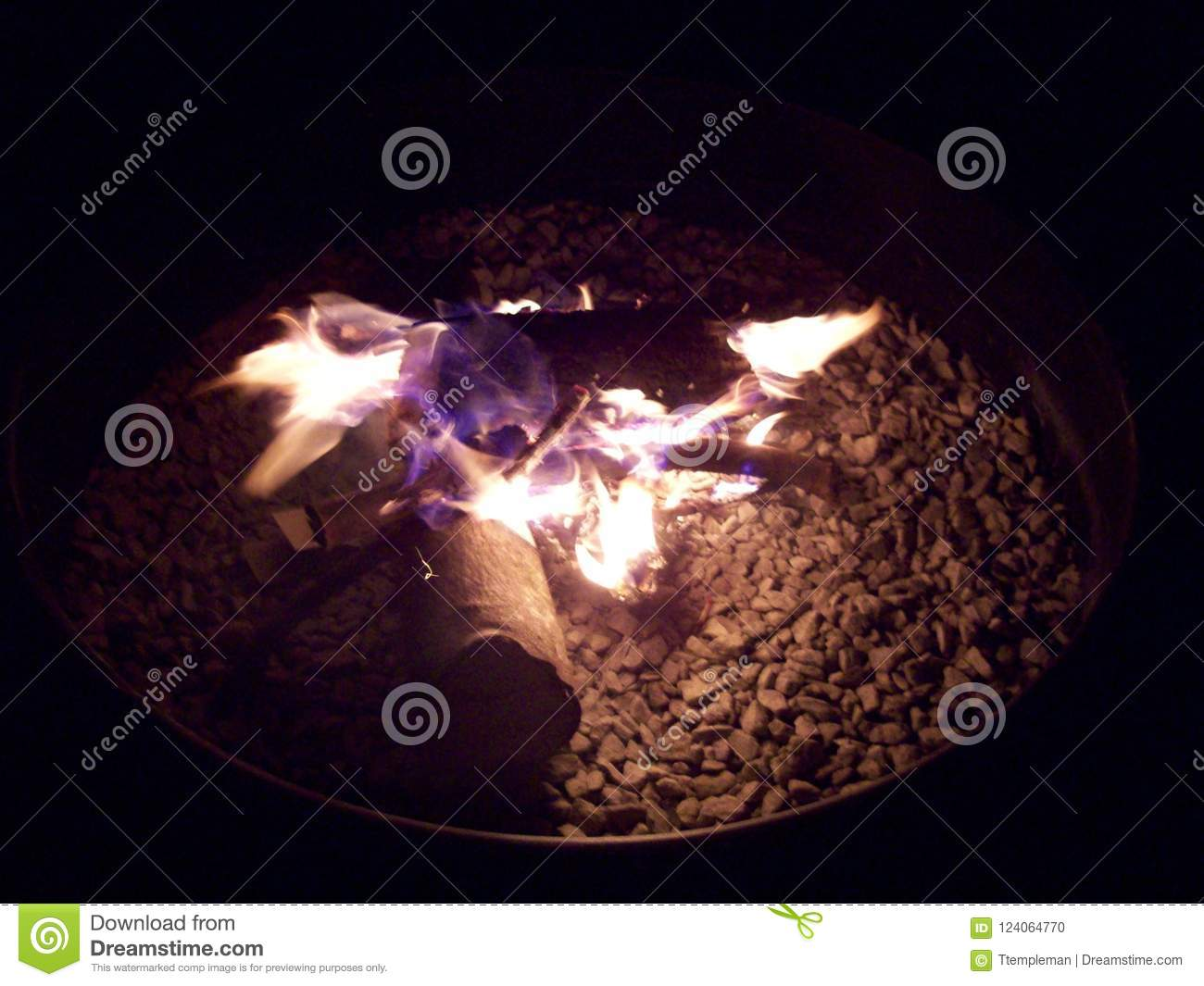 5c6206d0a5387 Blue and yellow flames flicker and dance in a backyard fire pit on a summer  night. Perfect fire for s`mores
