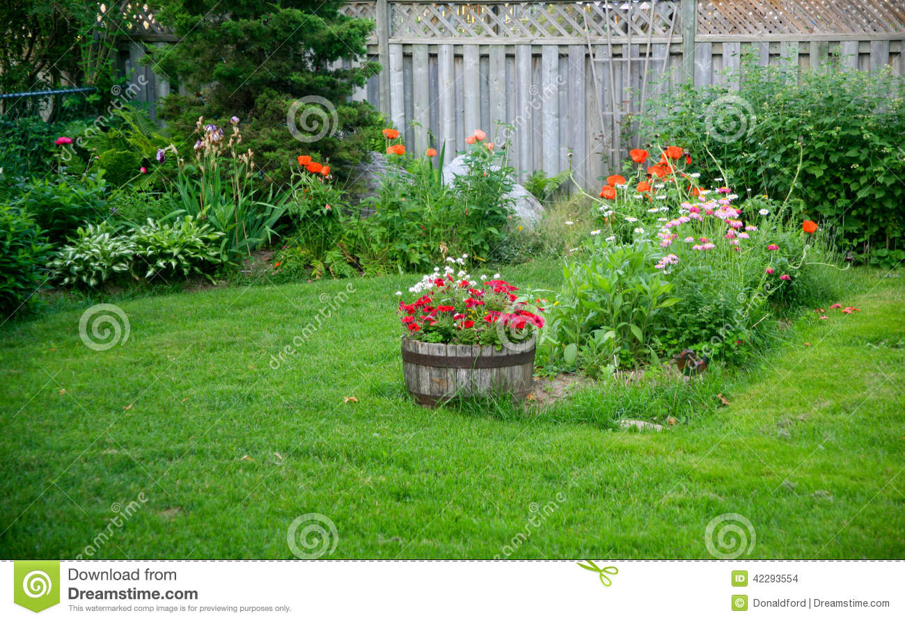 backyard garden with flowers growing around the edge and fence a
