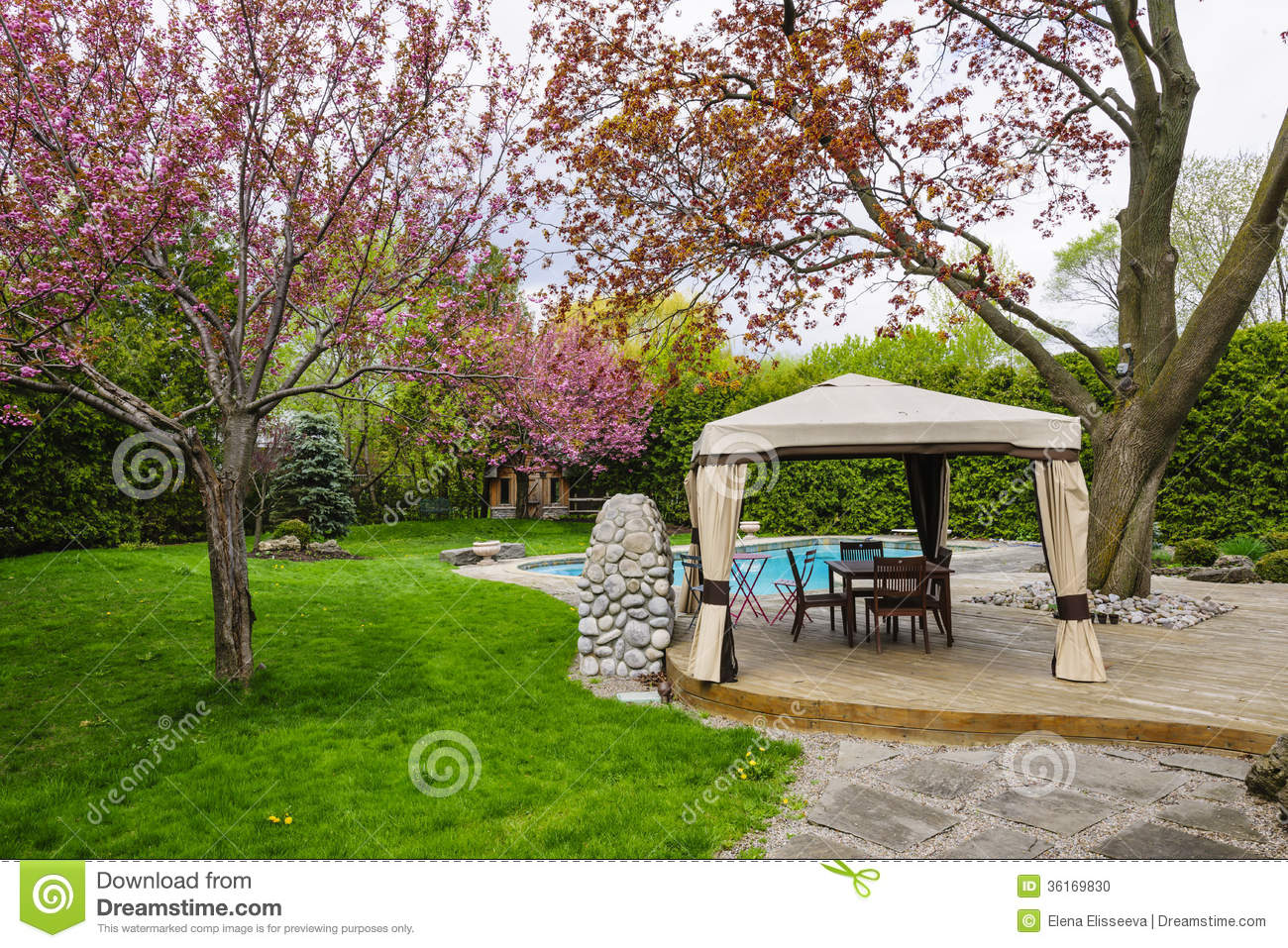 Residential backyard with gazebo, deck, stone patio and swimming pool.