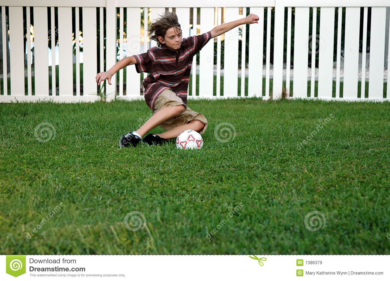 boy playing soccer in the backyard