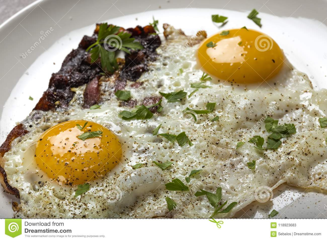 Bacon and eggs with ground pepper and parsley leaves