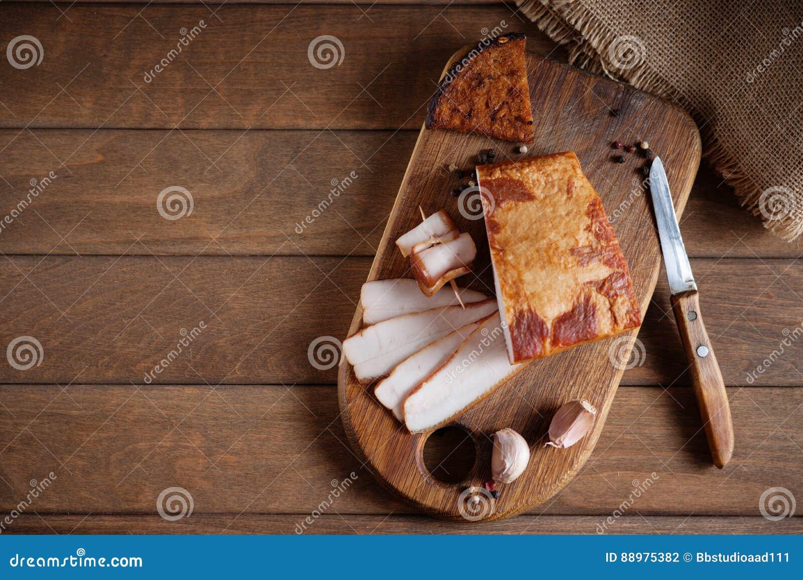 Bacon fumado, faca e pão cortado