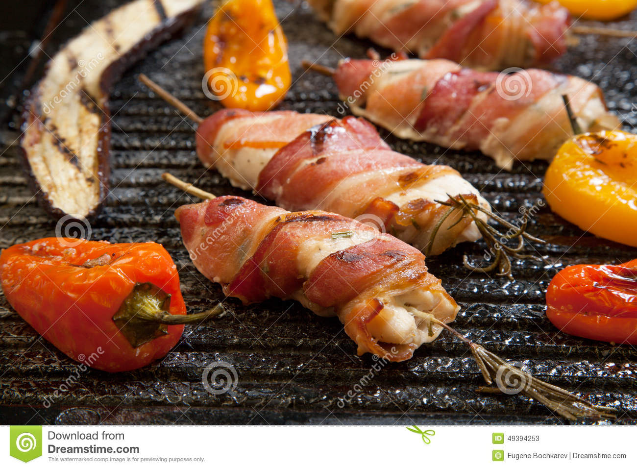 Grilled bacon-wrapped chicken tenders with lemon and rosemary on the ...