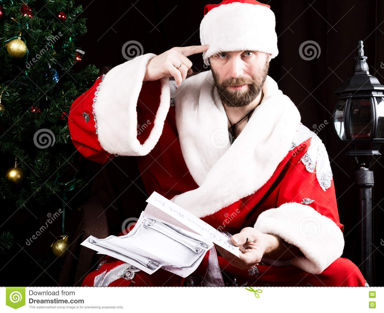 Bad brutal Santa Claus discontentedly reads letter with wishes and twists finger at a temple, on the background of