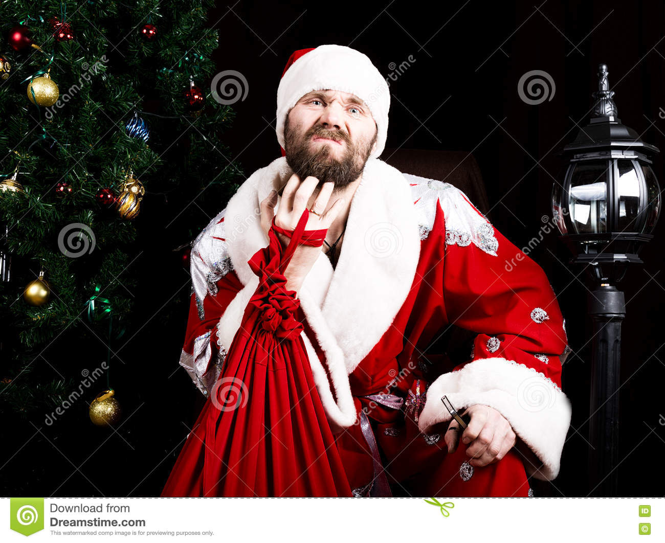 Bad brutal Santa Claus holding the bag with gifts and scratching his beard on the background of Christmas tree