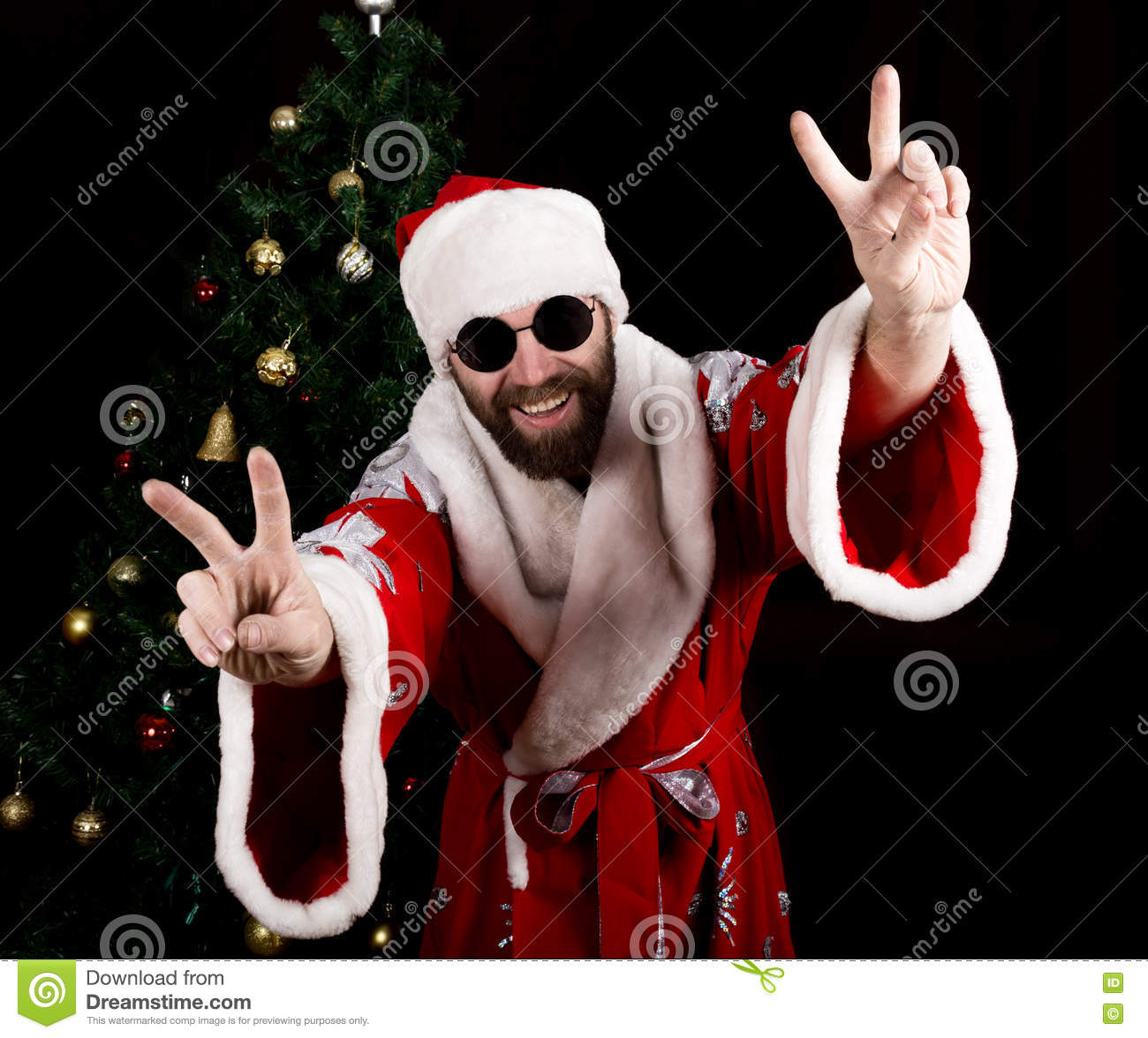 Bad brutal Santa Claus smiles and showing finger sign on the background of Christmas tree