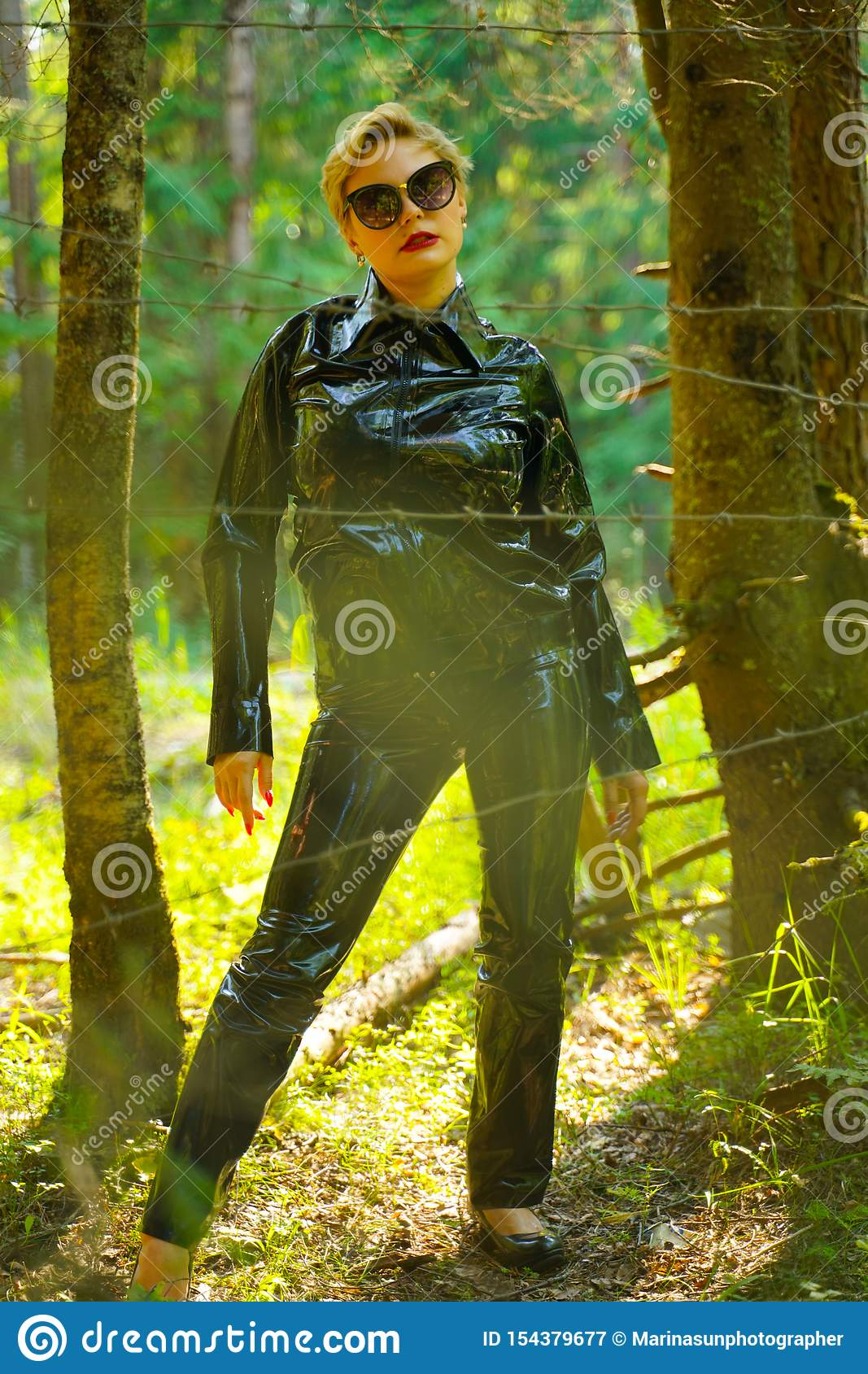 Latex rubber fashion woman walking in the forest