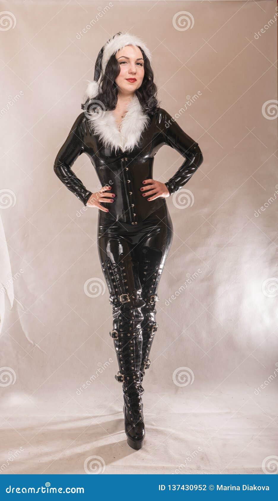 Bad kinky black satna girl posing in latex rubber costume with white fur on dark colorful studio background