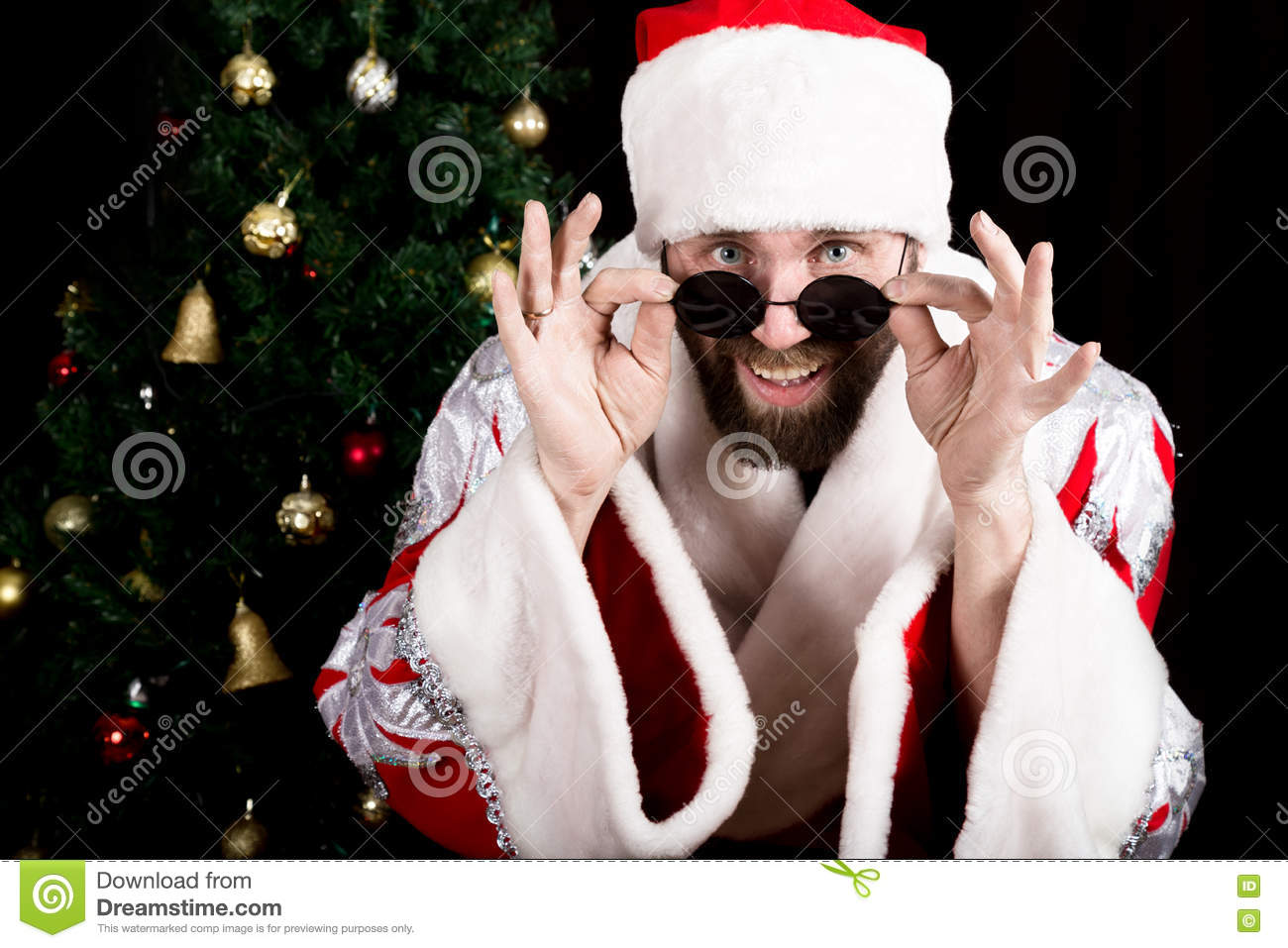 Bad rastoman Santa Claus holds round glasses and smiles, on the background of Christmas tree. different funy emotions