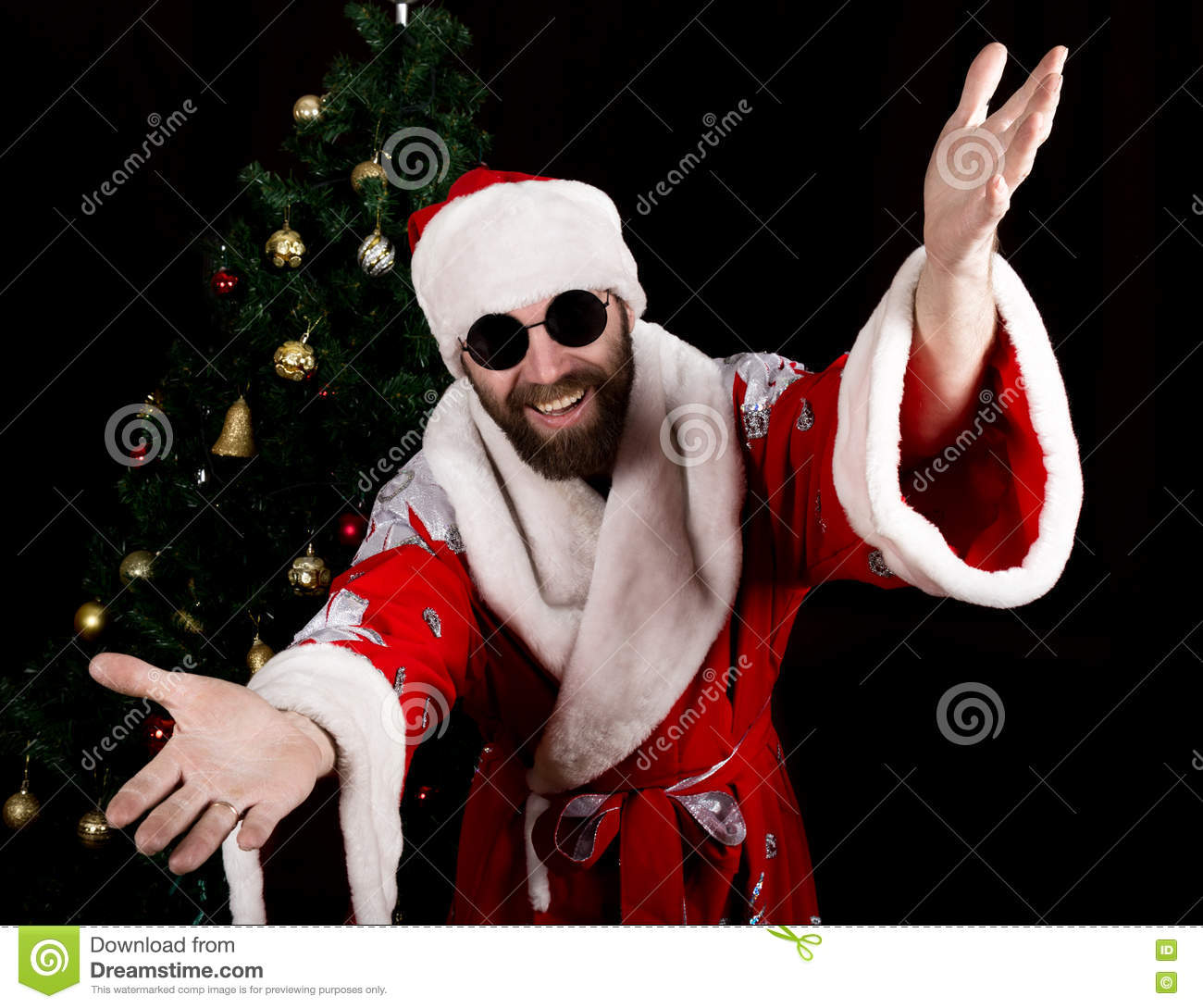 Bad rastoman Santa Claus smiles and spread his hands in different side on the background of Christmas tree