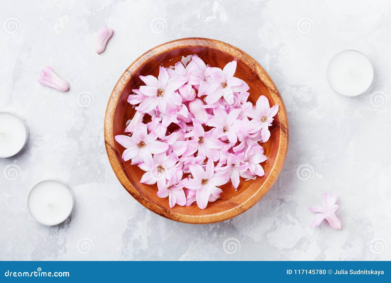 Badekurort und Wellnesszusammensetzung von parfümierten rosa Blumen wässern in der hölzernen Schüssel und in den Kerzen auf graue