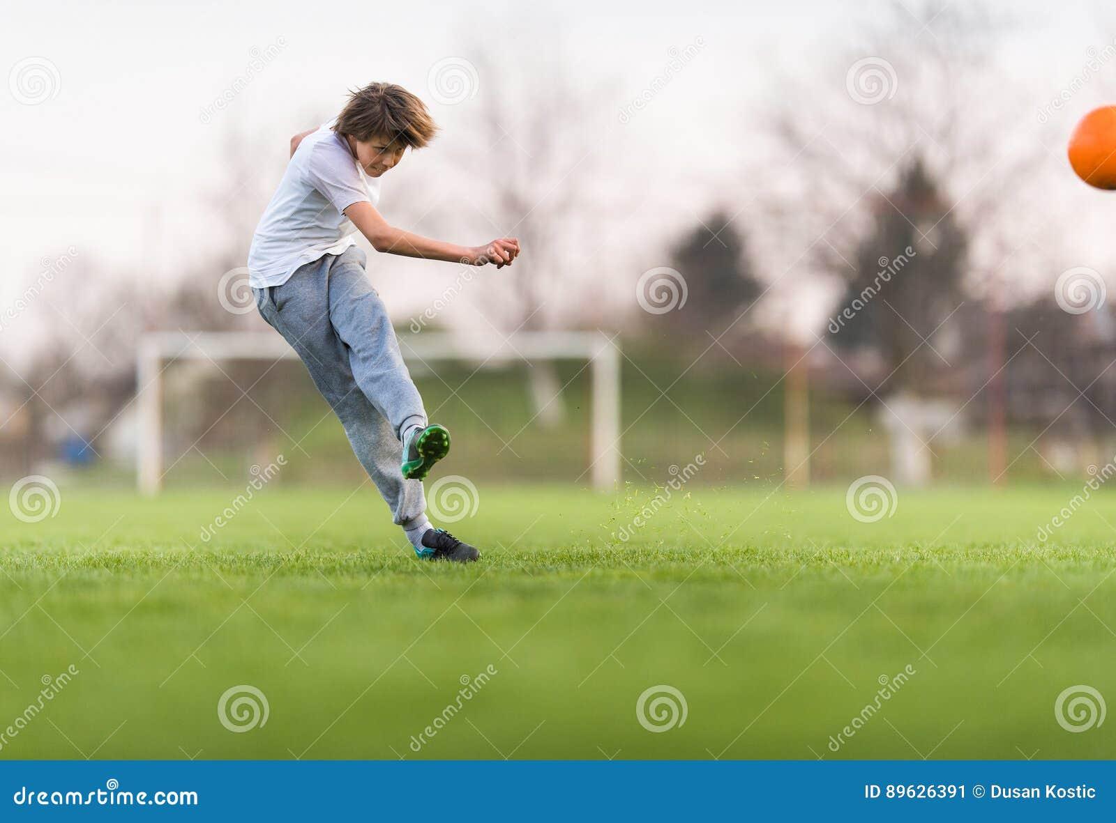 Badine le football du football - joueur d enfants sur le terrain de football
