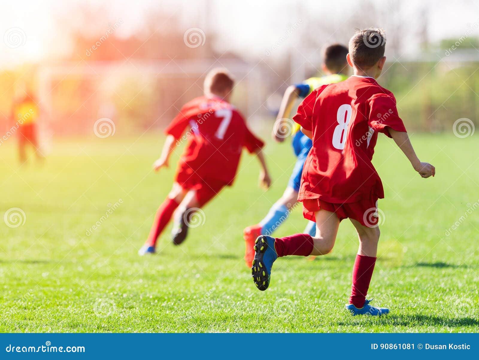 Badine le football du football - les joueurs d enfants sont assortis sur le terrain de football