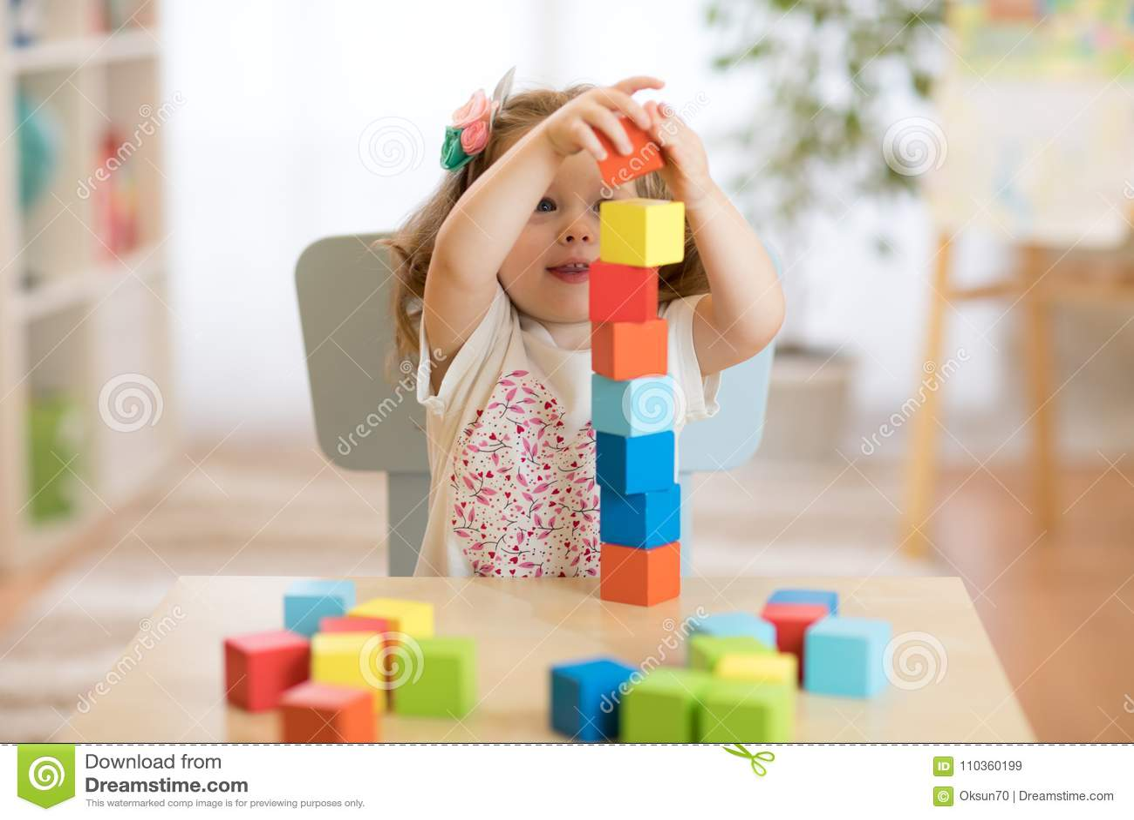 Badinez la fille jouant avec des jouets de bloc au centre de soins de jour