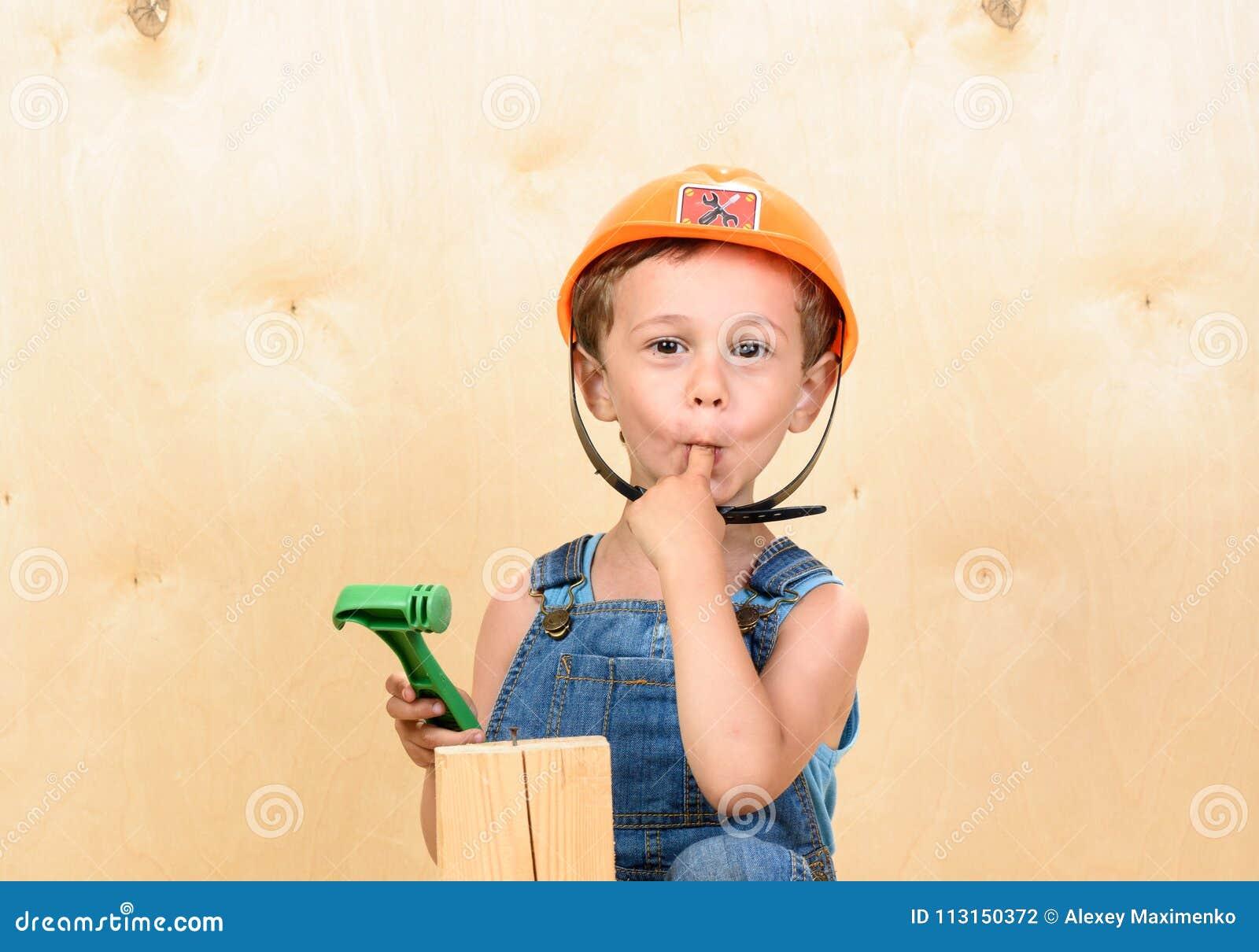 Badinez le garçon en tant que constructeur drôle tenant le doigt dans la bouche après l avoir frappée avec le marteau