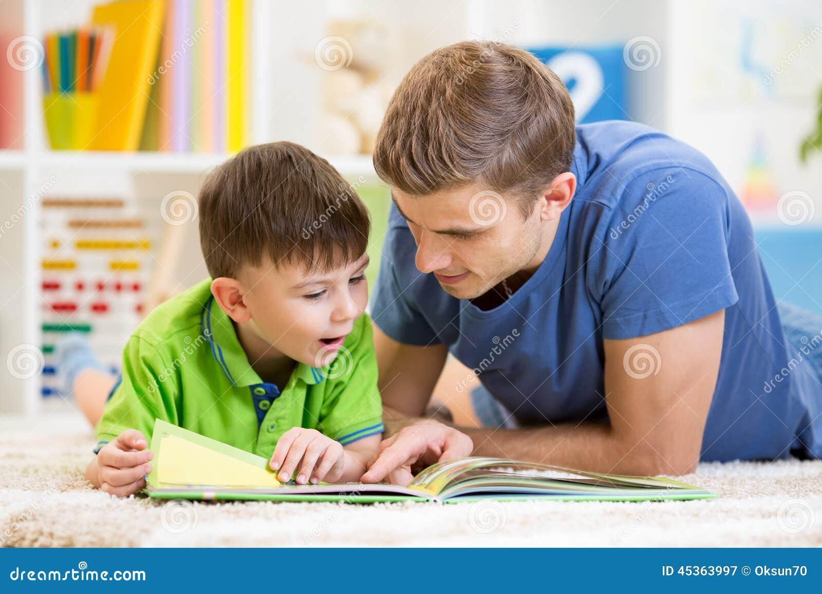 Badinez le garçon et son père a lu un livre sur le plancher à la maison