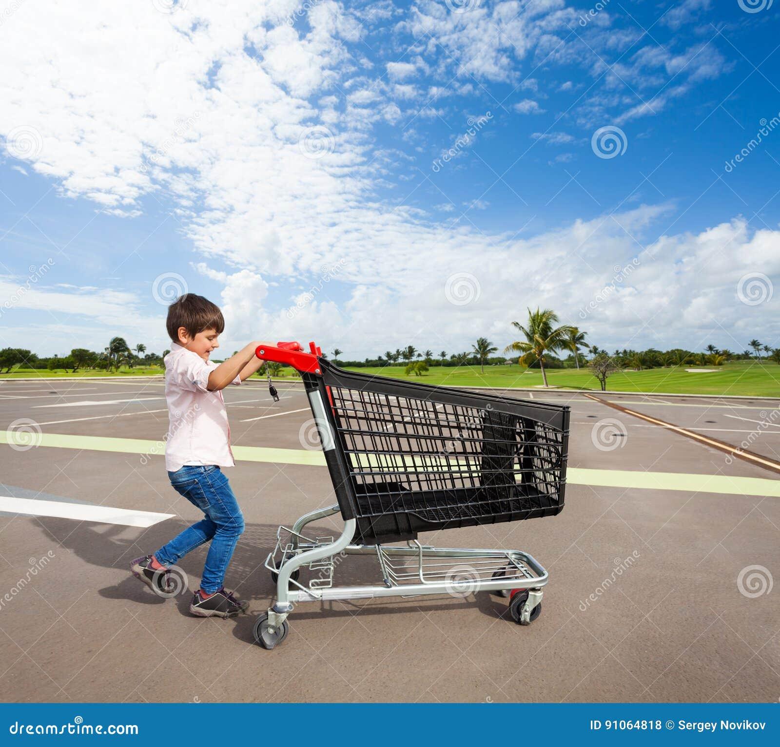 Badinez le garçon poussant le caddie vide au parking