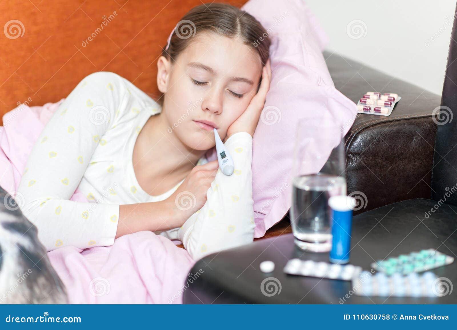Badinez se situer froid de crochet dans le lit avec le temperatu de mesure de thermomètre