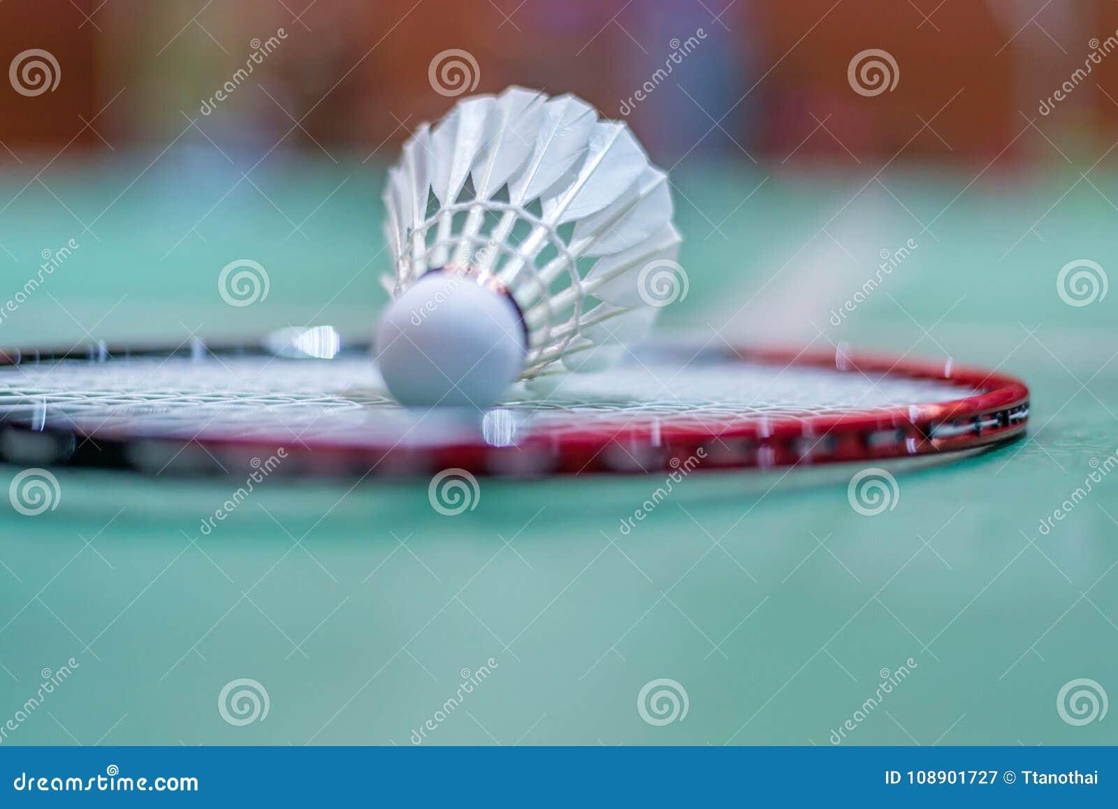 Badmintonfjäderboll på badmintonracket på golv