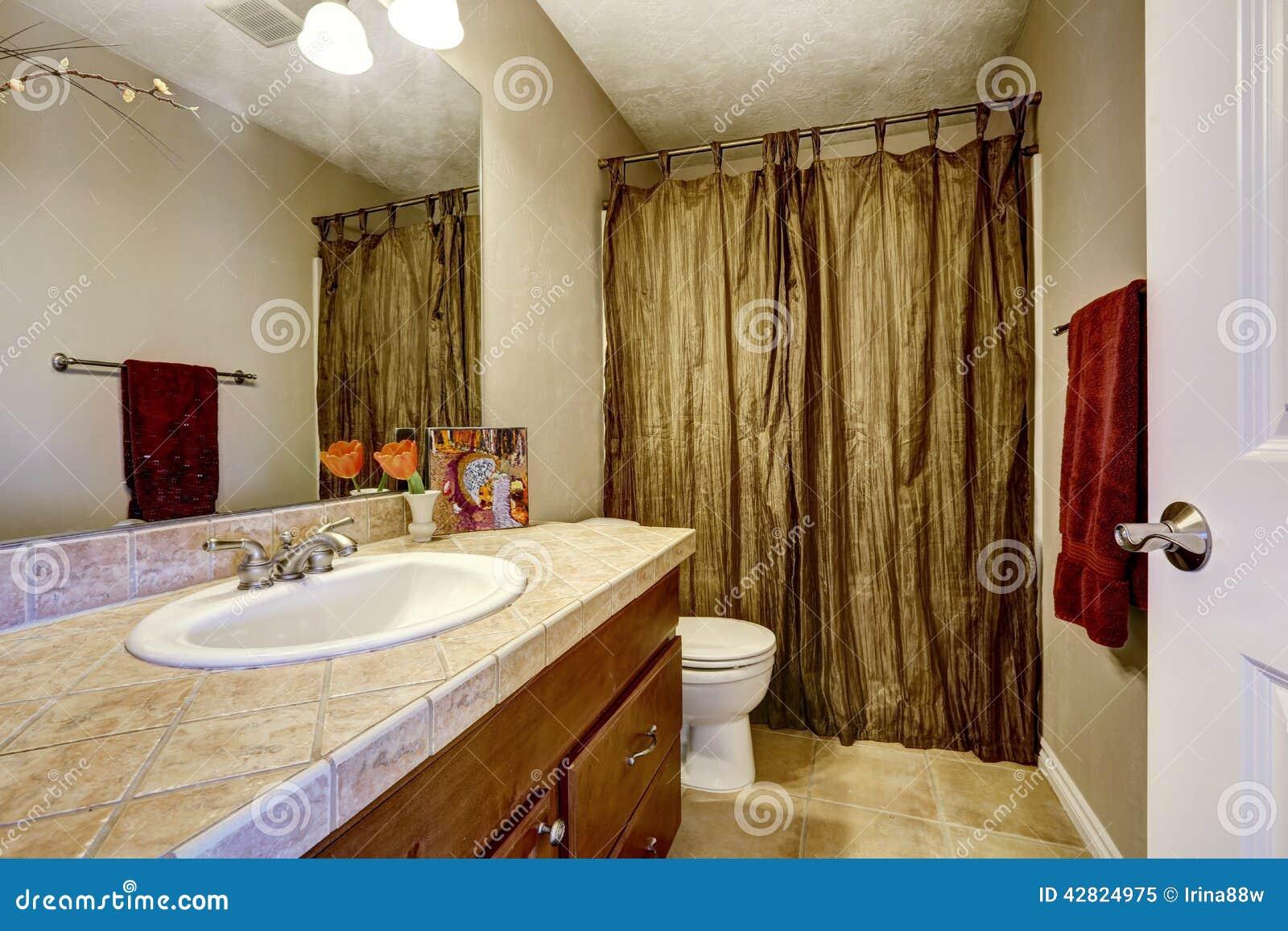 Badrum med bruna kabinett  och senapgardiner arkivfoto   bild ...
