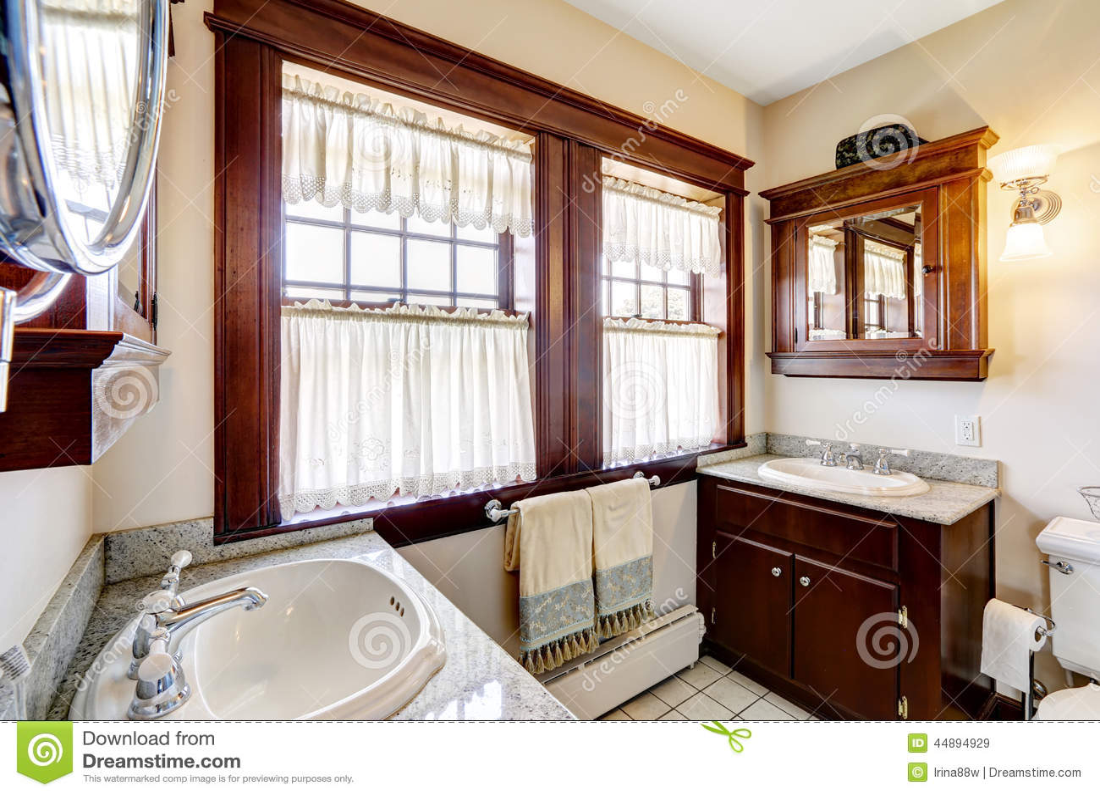 Badrum med kabinetter för mörk brunt och det stora fönstret ...