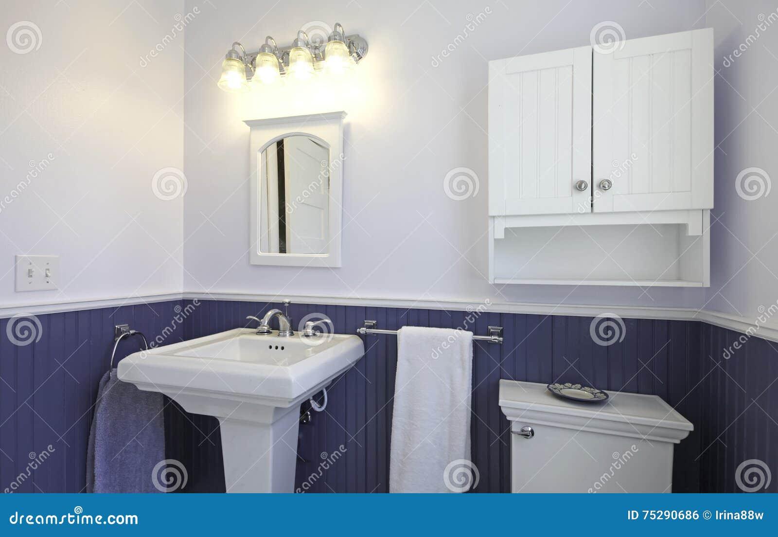 Badrum med det bruna tegelplattagolvet och ljus   blåa väggar ...