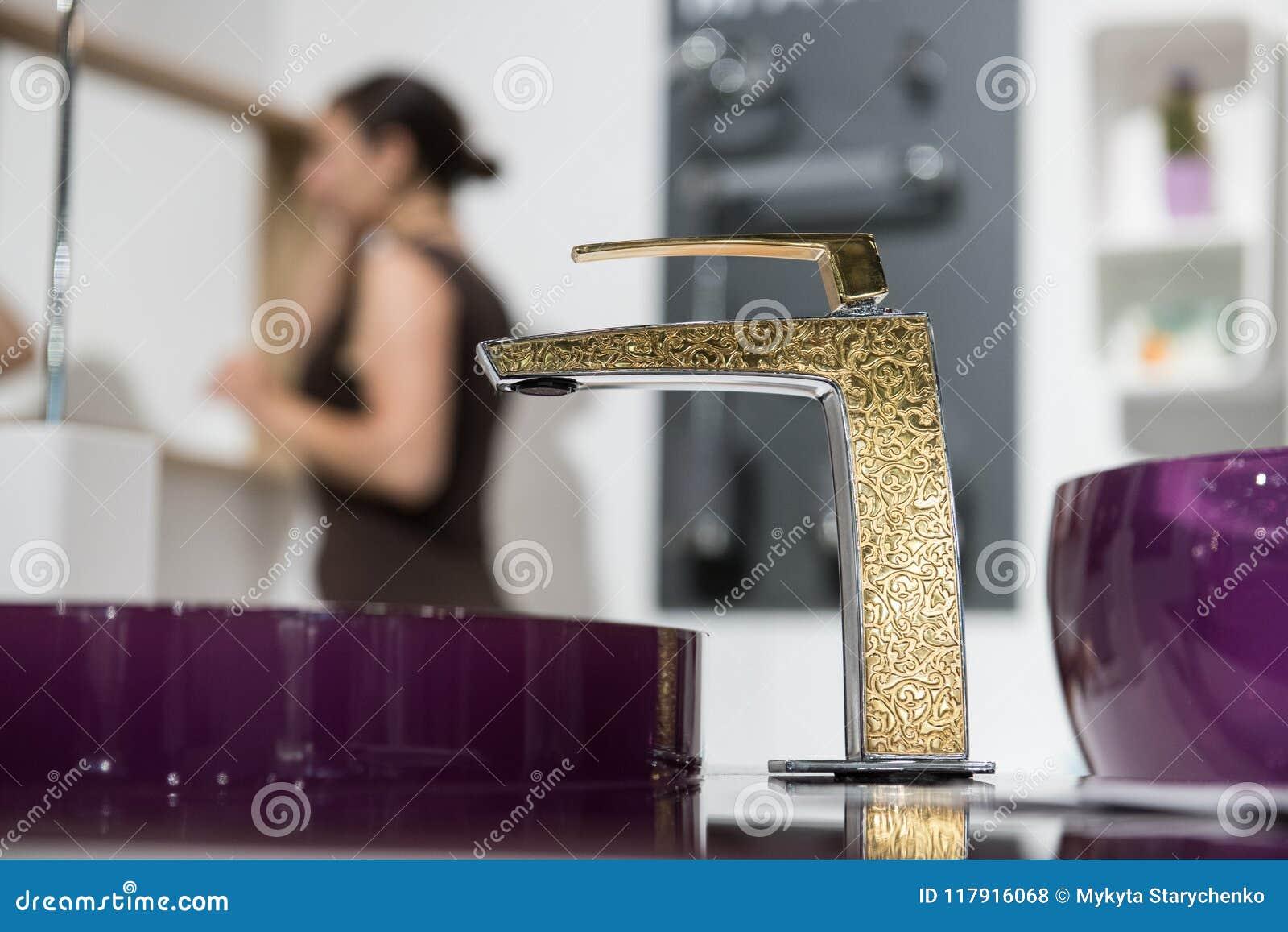 Badrumdetalj i nytt lyxhem: vask och guld- vattenkran med partisk sikt av den near spegeln för kvinna