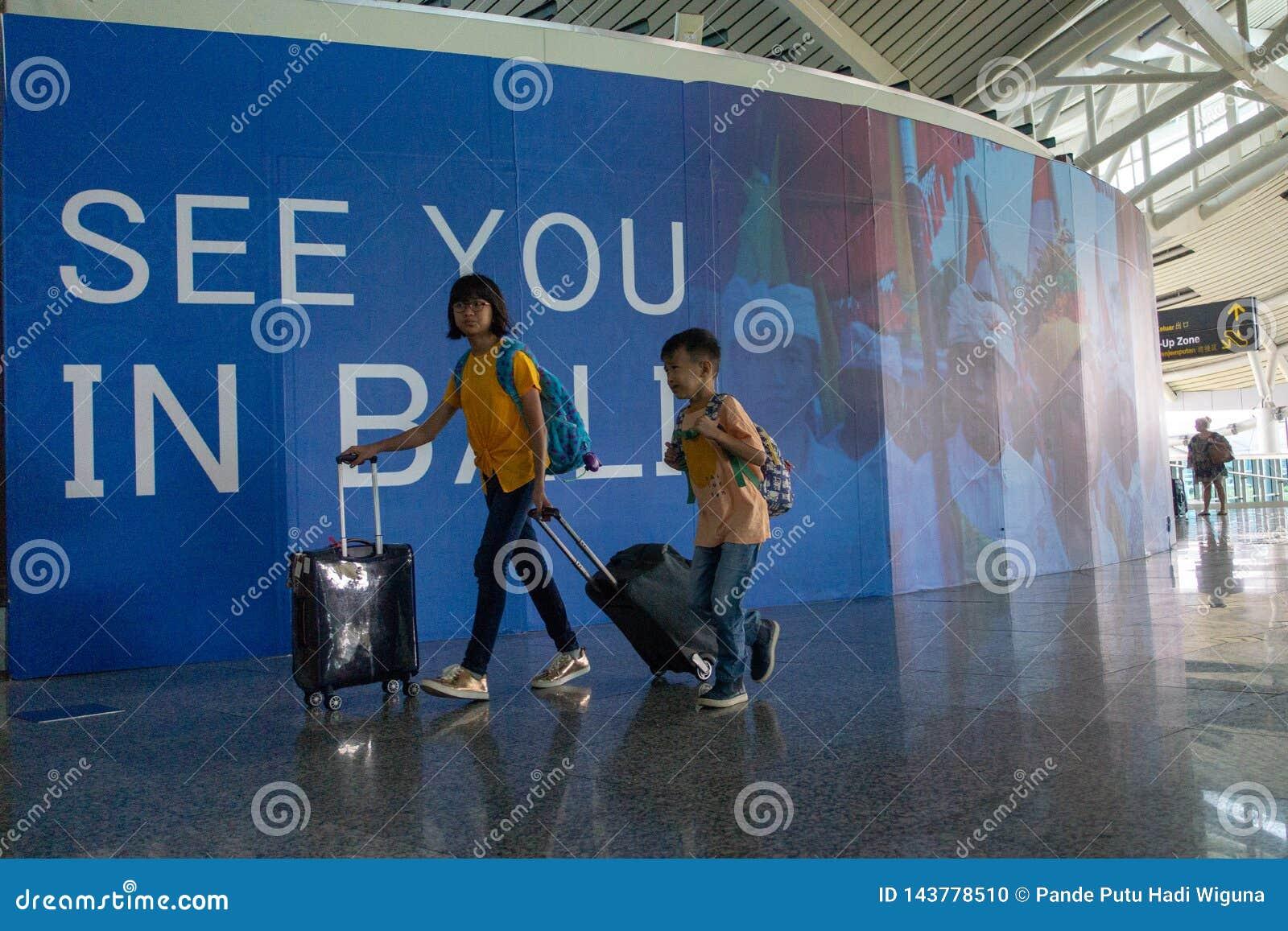 BADUNG,BALI/INDONESIA 6月25日2018年:两年轻旅行家给离开终端带来他们的手提箱在拉伊巴克罕巴厘岛