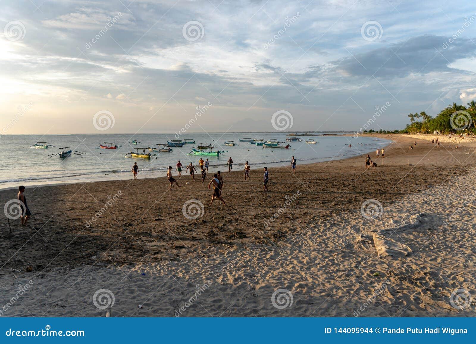 BADUNG,BALI/INDONESIA-APRIL 02 2019年:亚洲少年戏剧橄榄球或足球在海滩与日落或金黄小时背景