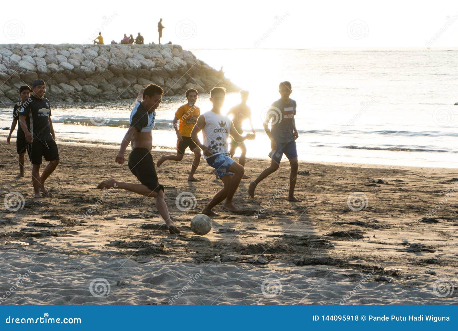 BADUNG, BALI/INDONESIA- 2-ОЕ АПРЕЛЯ 2019: Азиатские футбол или футбол игры подростка на пляже с предпосылкой захода солнца