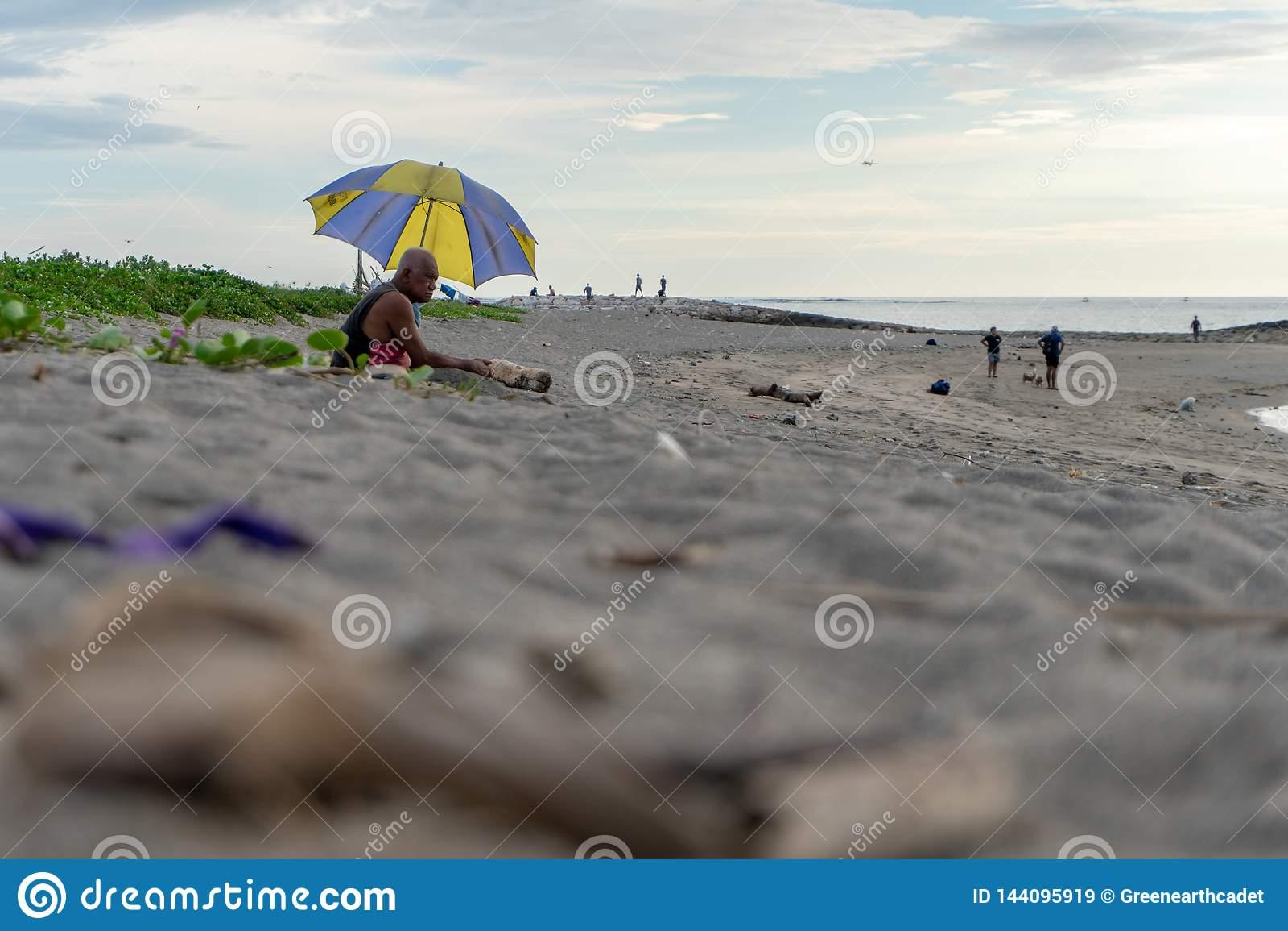 BADUNG, BALI/INDONESIA- 2-ОЕ АПРЕЛЯ 2019: Старик сидит на песке и наслаждается загорать