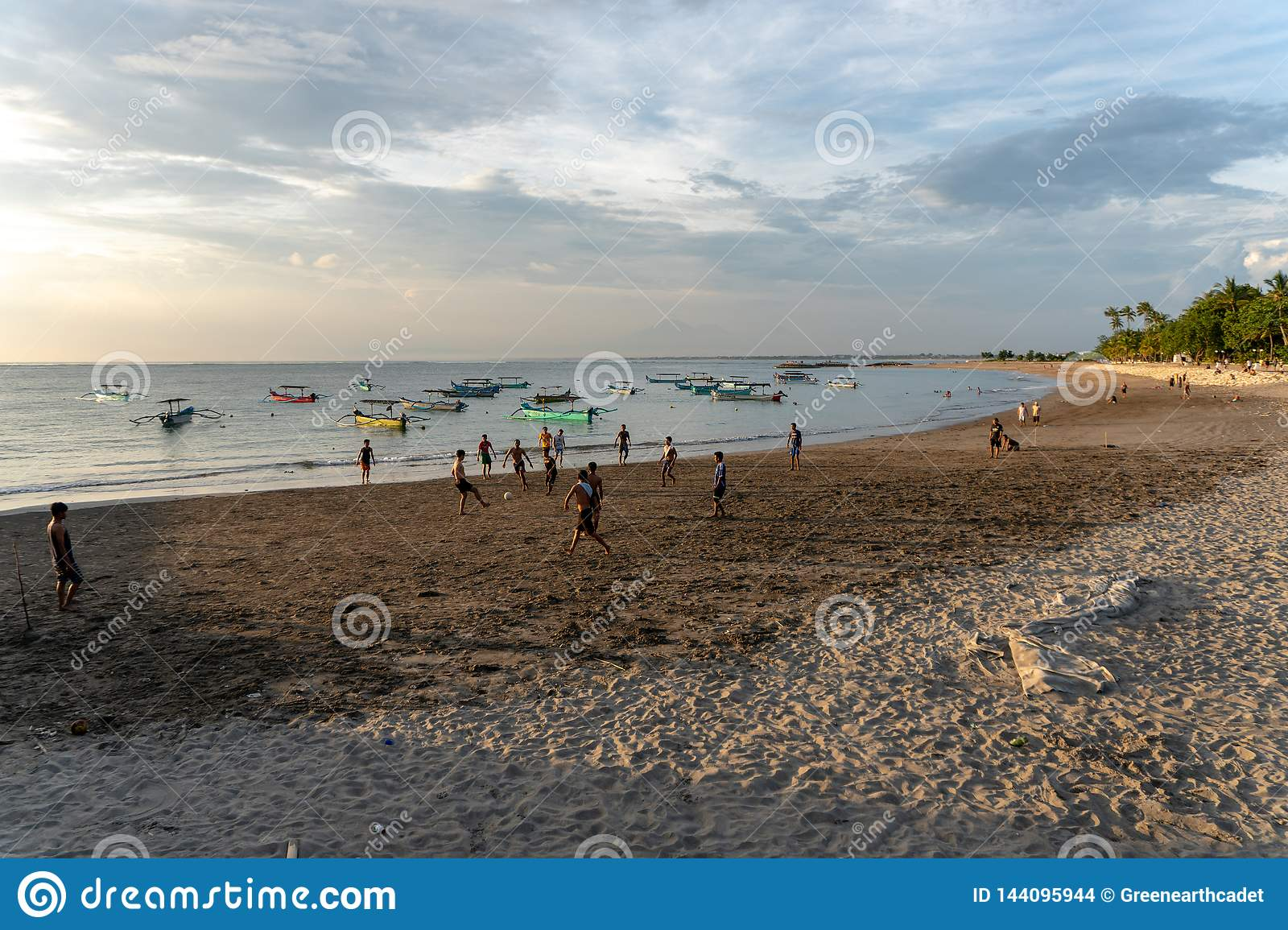 BADUNG,BALI/INDONESIA-APRIL 02 2019: Asian Teenager play football or soccer at the beach with sunset or golden hours background
