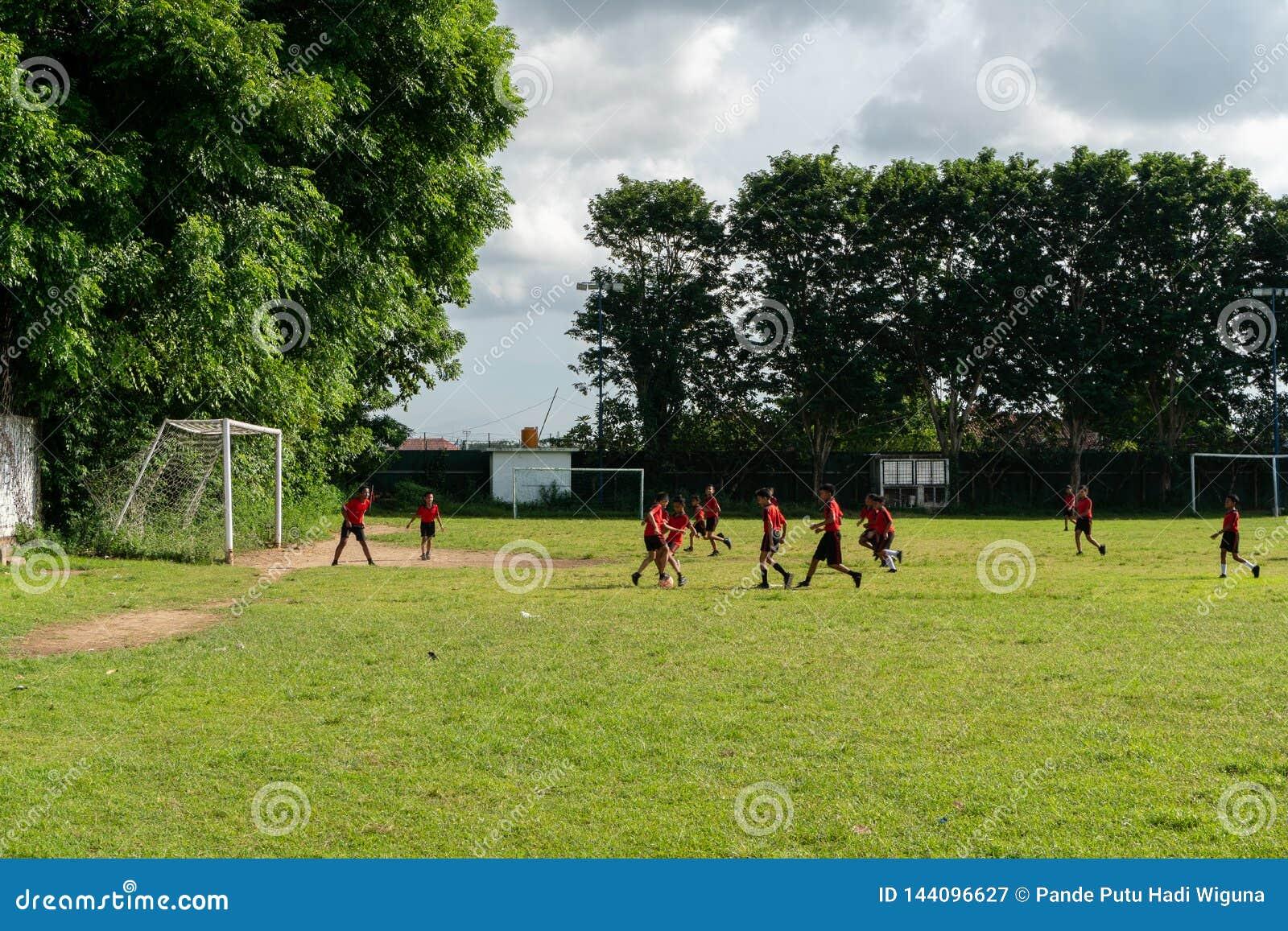BADUNG, BALI/INDONESIA- 5. APRIL 2019: Grundlegender Studentenspielfußball oder -fußball auf dem Feld mit rotem Trikot