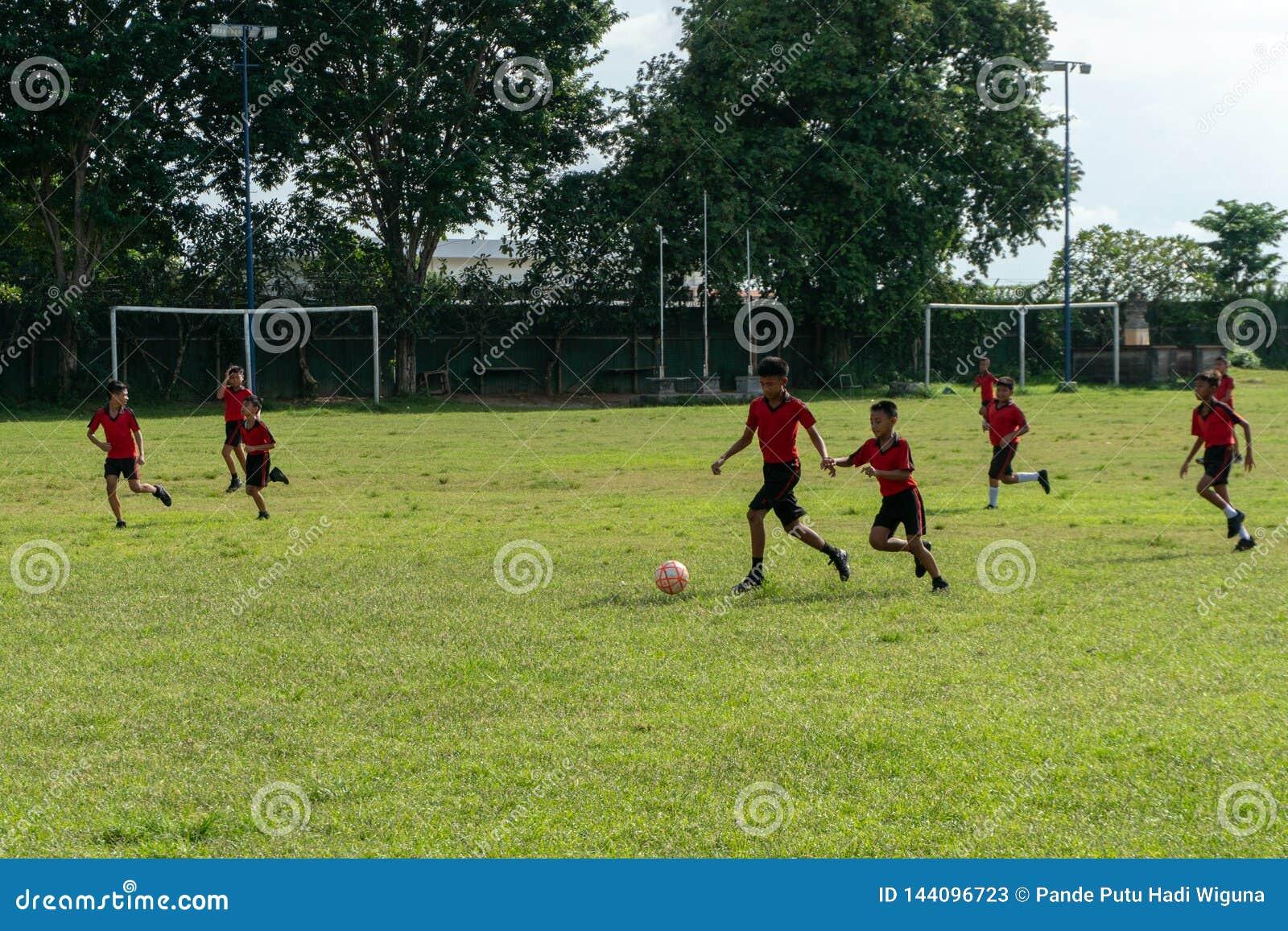 BADUNG, 05 BALI/INDONESIA-APRIL 2019: Het de elementaire voetbal of voetbal van het studentenspel op het gebied met rood Jersey