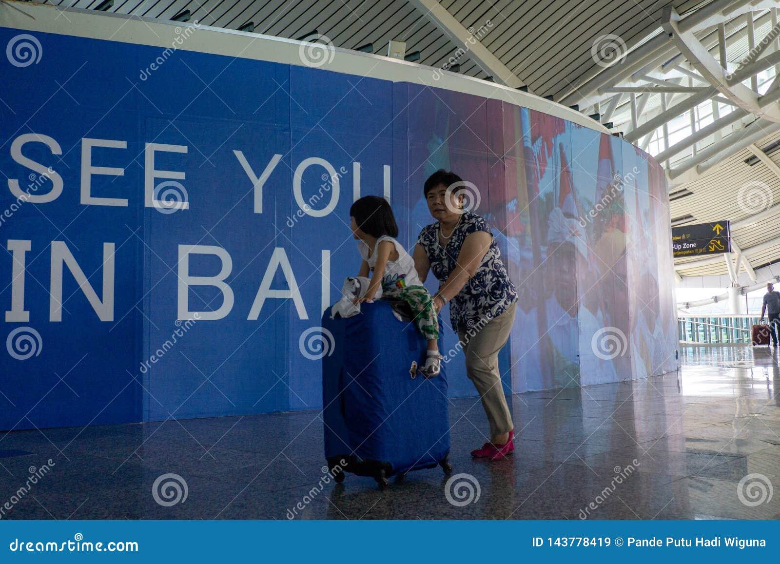 BADUNG, BALI/INDONESIA- 25 de junho de 2018: Mãe e sua filha pequena para trazer sua mala de viagem ao terminal da partida em Ngu