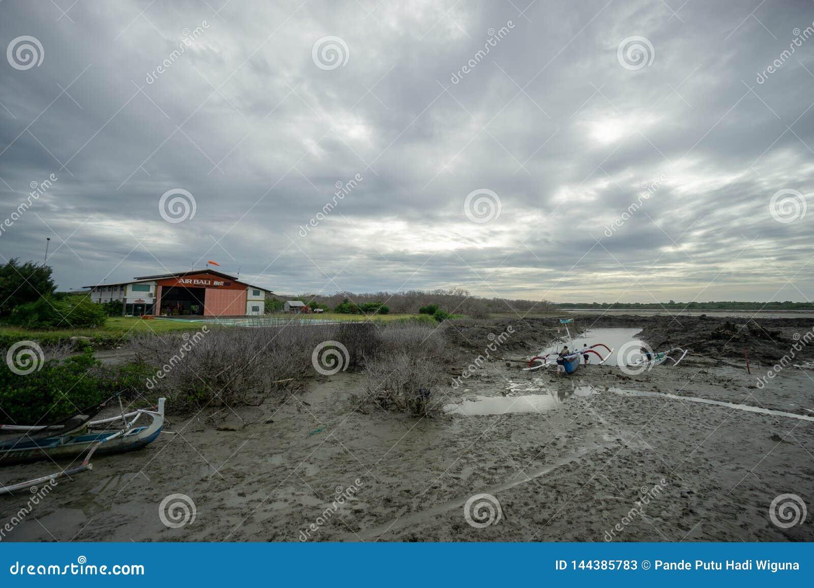 BADUNG, BALI/INDONESIA- 8 DE MARZO DE 2019: Barco del pescador pegado en el fango debido a marea baja en Benoa