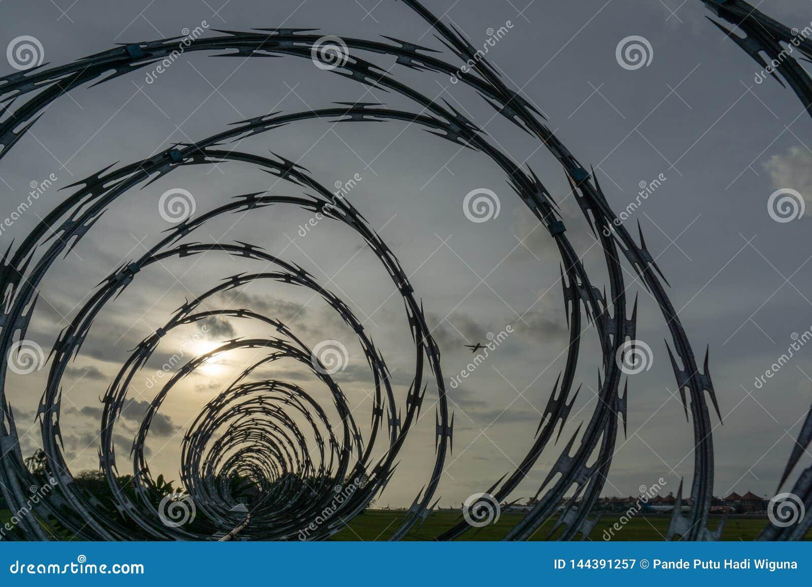 BADUNG, BALI/INDONESIA- 1ER JANVIER 2017 : La vue d aéroport des barrières barbelées quand le soleil se couche