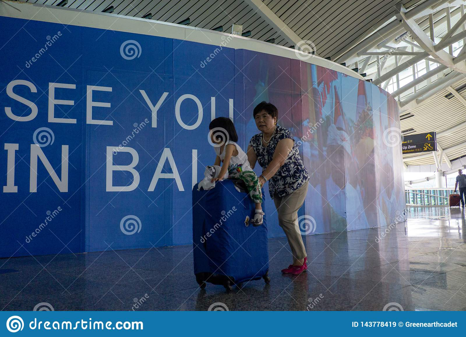 BADUNG, BALI/INDONESIA- 25 juin 2018 : Mère et sa petite fille apporter leur valise au terminal de départ chez Ngurah Rai Bali