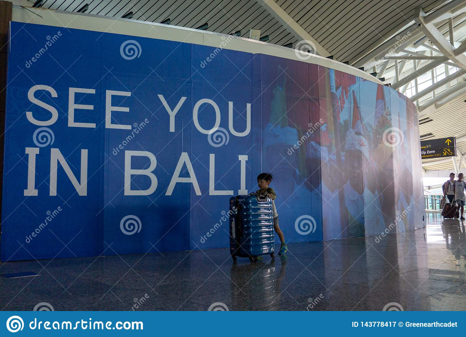 BADUNG, BALI/INDONESIA- 25 juin 2018 : Peu garçon apporte sa propre seule valise au terminal de départ dans Ngurah Rai Bali