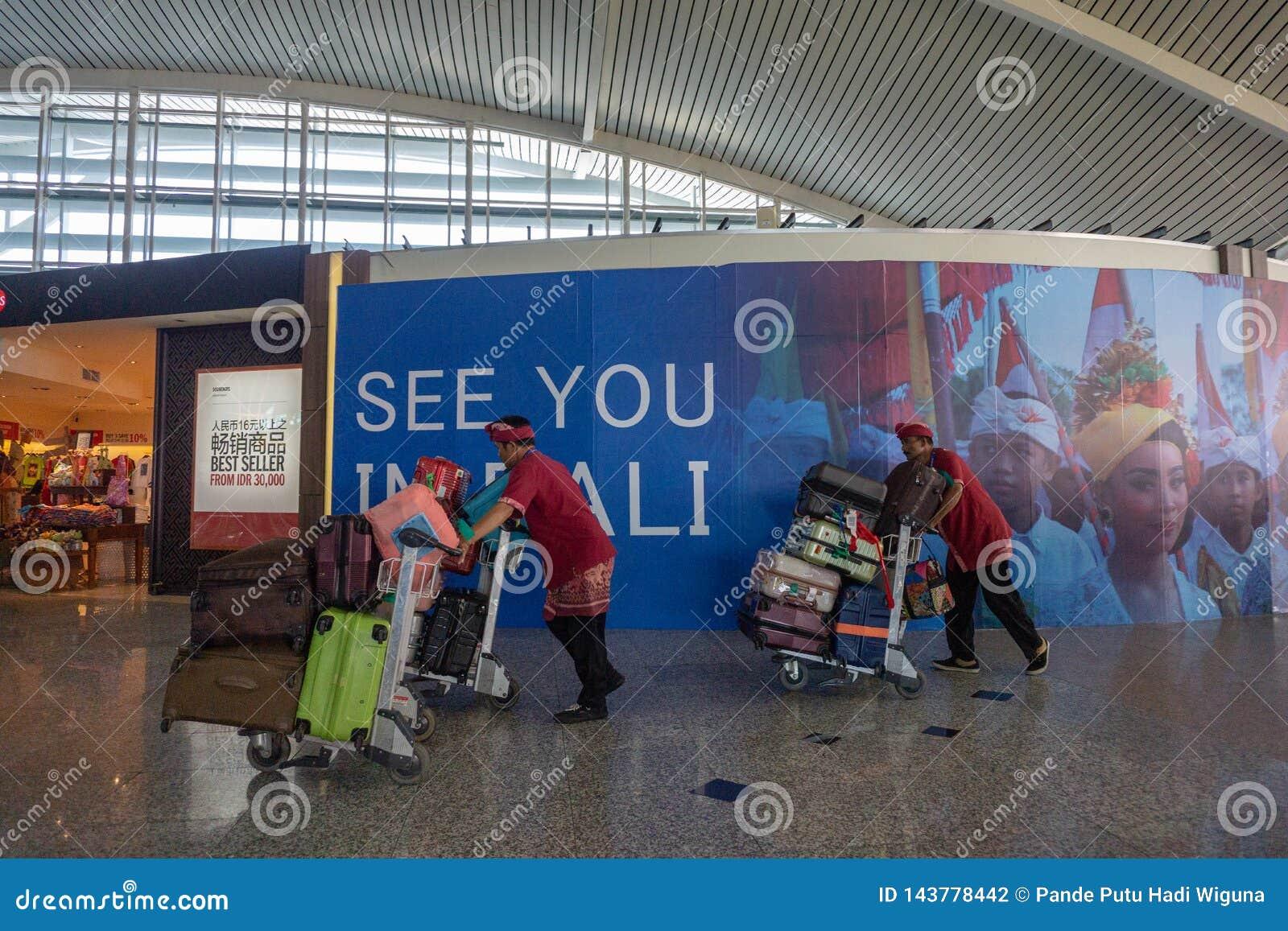 BADUNG BALI/INDONESIA-June 25 2018: Portvakter kommer med passagerareresväskor till avvikelseterminalen
