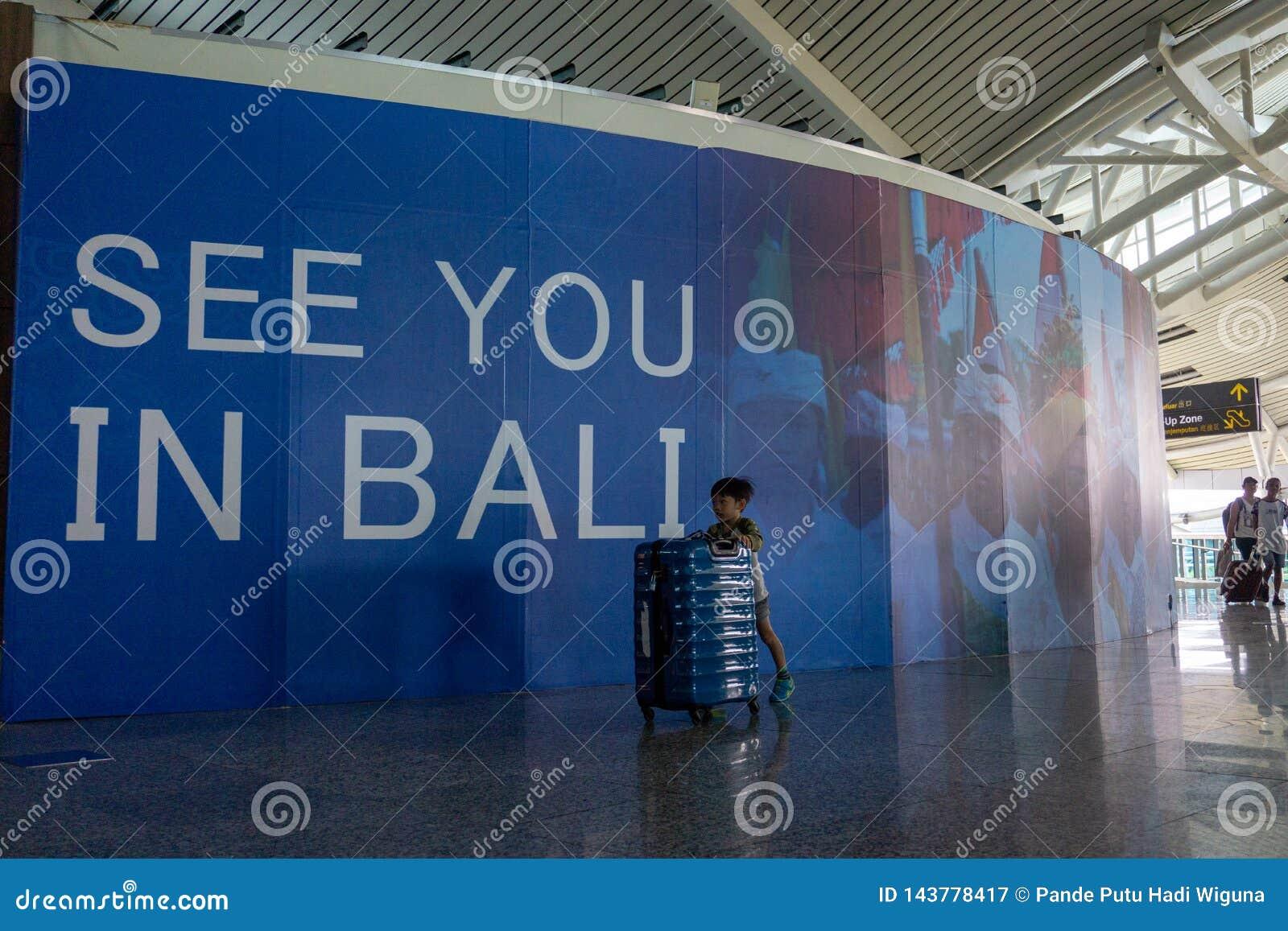 BADUNG BALI/INDONESIA-June 25 2018: Pysen kommer med hans egen resväska bara till avvikelseterminalen i Ngurah Rai Bali