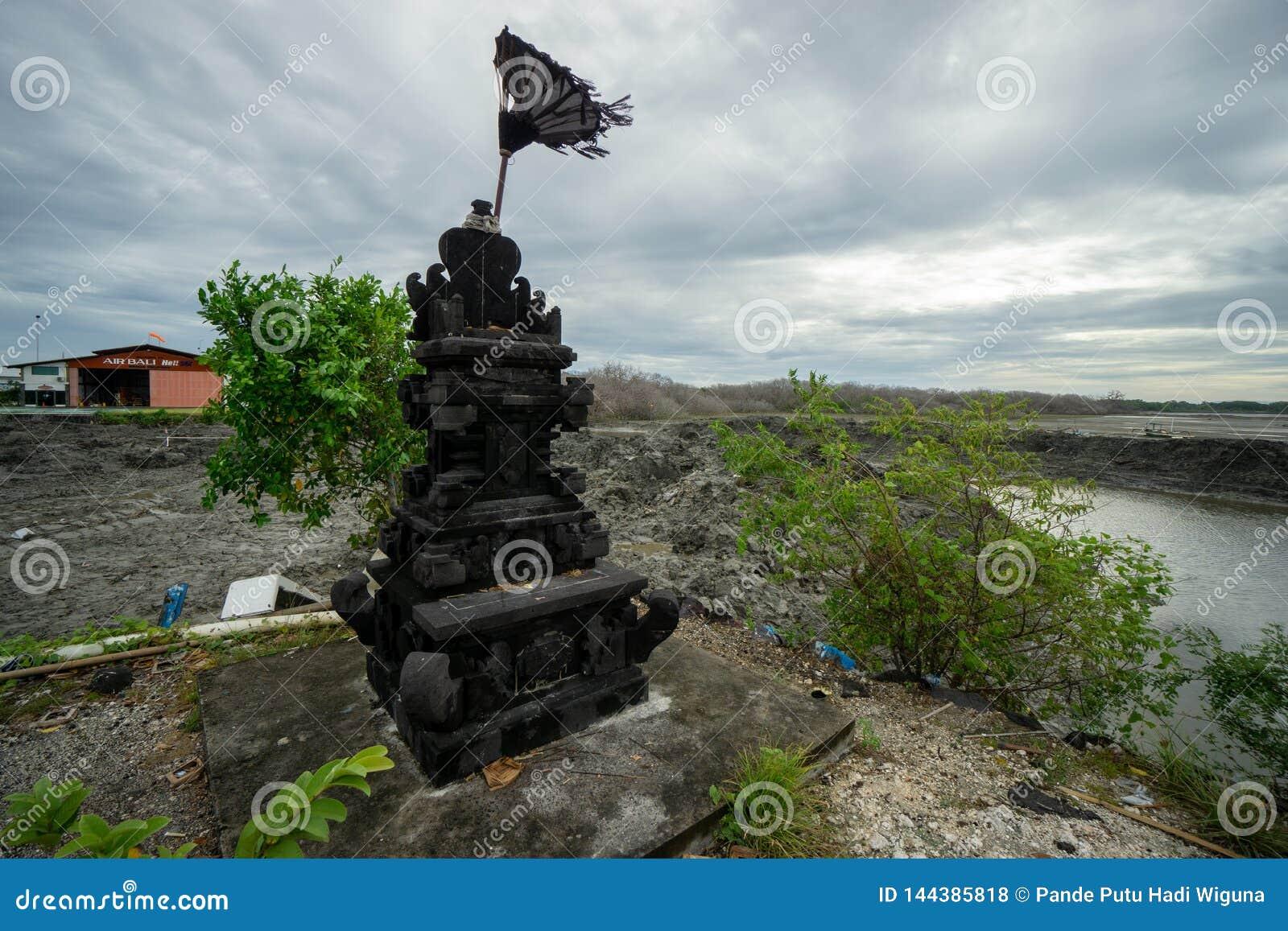 BADUNG, 08 BALI/INDONESIA-MAART 2019: Zwart natuursteenstandbeeld voor het aanbieden van plaats