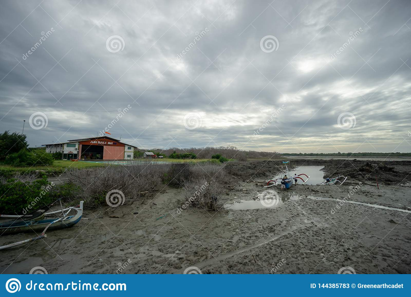 BADUNG,BALI/INDONESIA-MARCH 8 2019: Fisherman boat stuck on the mud because of low tide in Benoa
