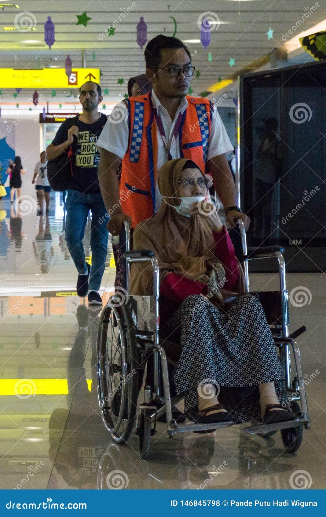 BADUNG/BALI-, 25. JUNI 2018: Flugzeugbesatzung hilft den kranken Passagieren, die einen Rollstuhl verwenden