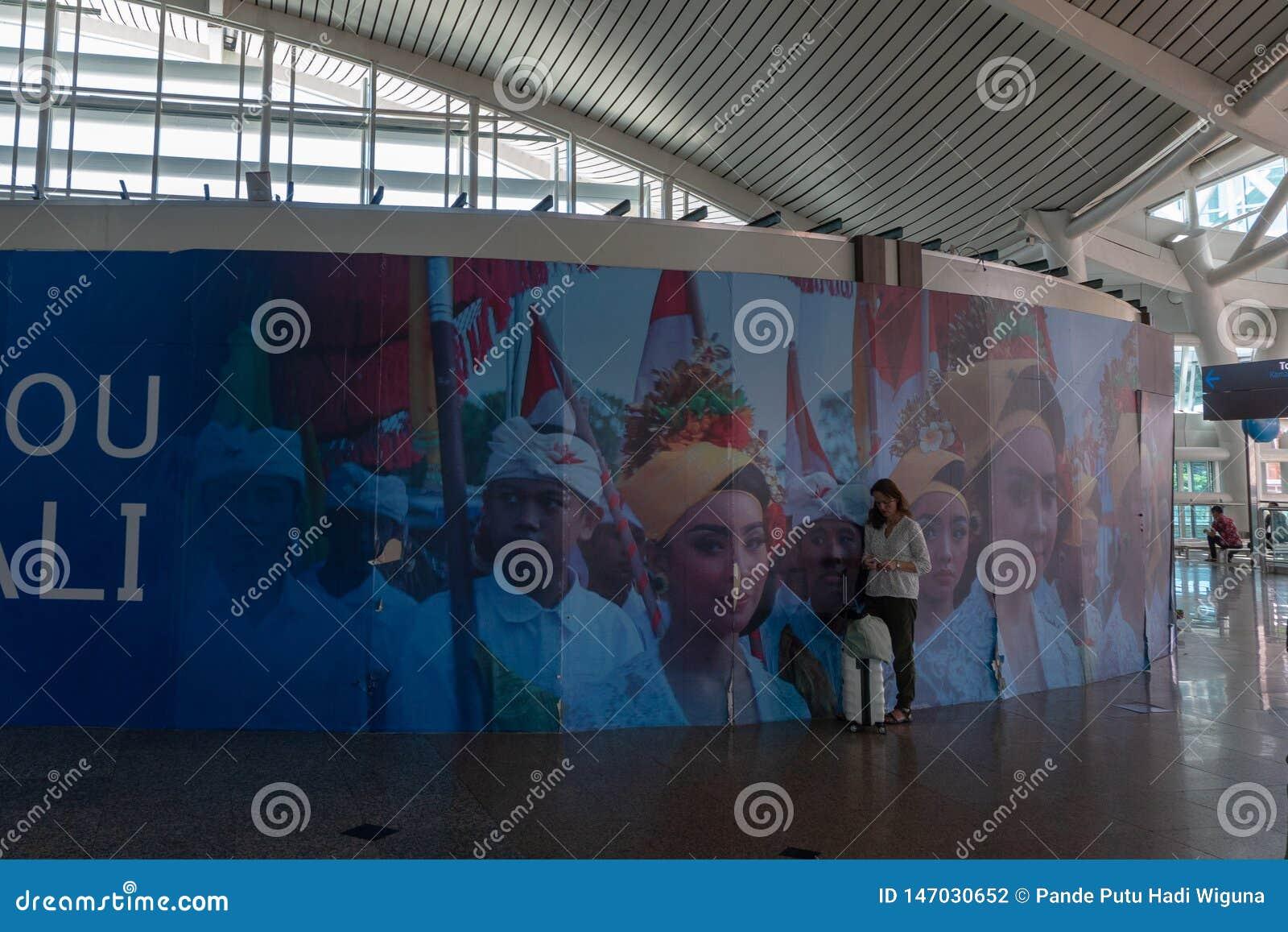 BADUNG/BALI-MARCH 28 2019: Żeński turysta, niesie walizkę, stał w terenie w balijczyka ornamentacyjnym lotnisku,