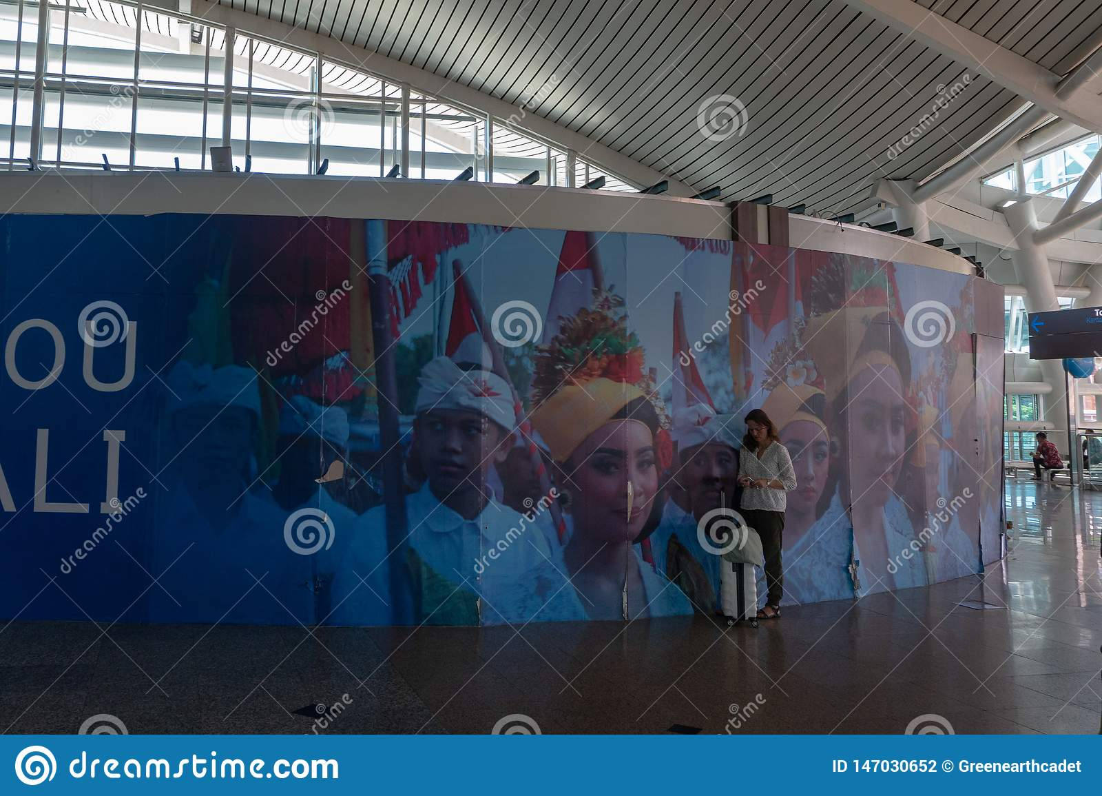 BADUNG/BALI-MARCH 28 2019: A female tourist, carrying a suitcase, was standing in an area in a Balinese ornamental airport,
