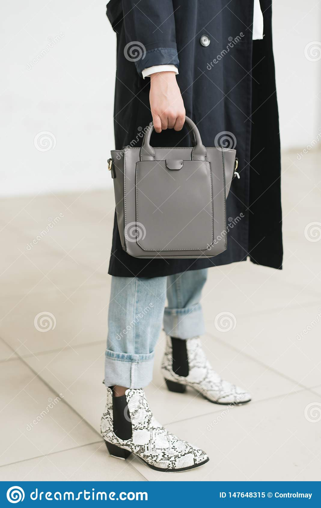 Bag in hand, blue jeans and blue raincoat