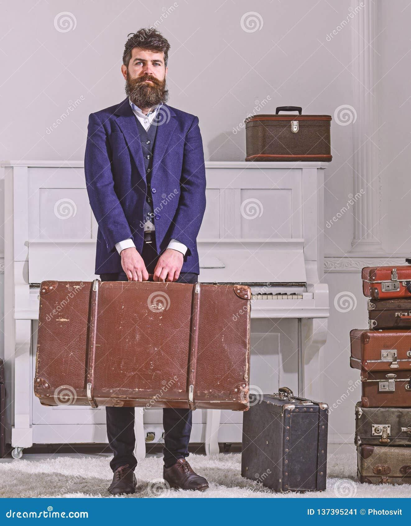Bagage och resande begrepp Macho stilfullt på strikt framsida står och bär den stora tappningresväskan Man handelsresande